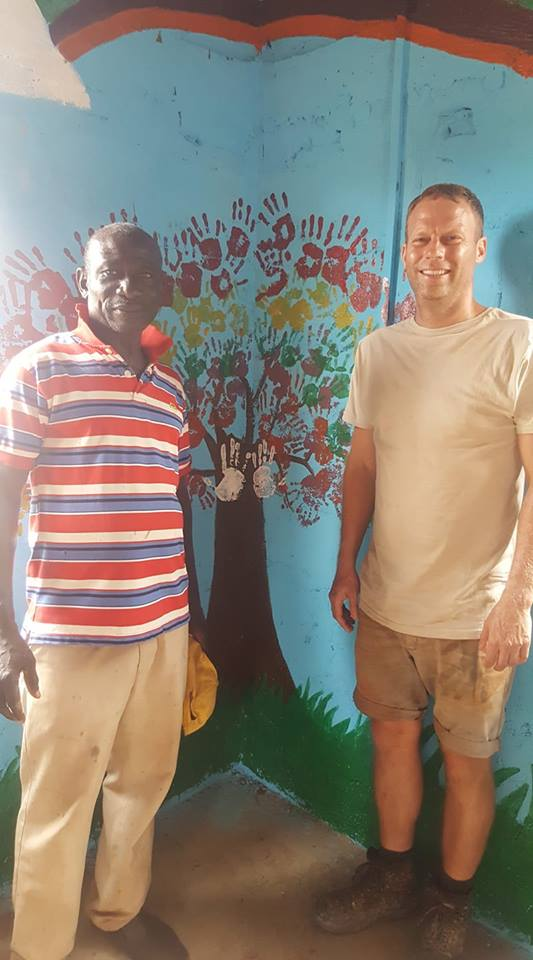 Officer Commanding Junior Leaders and the Chief of Obom complete the new creche community tree with the final two hand prints.