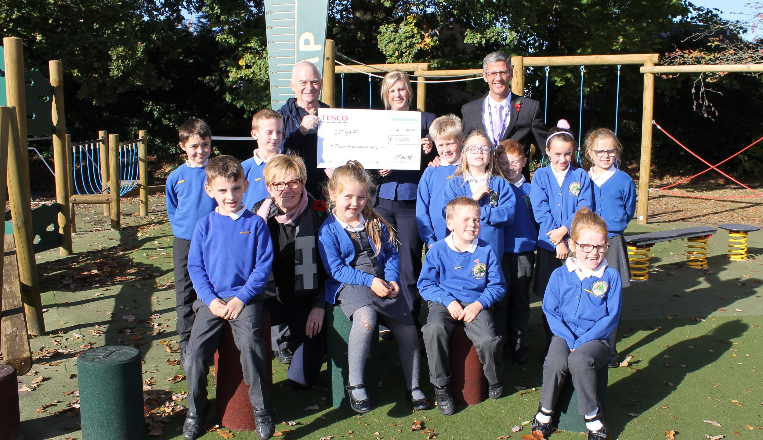 Pupils at Parley First School with (back left to right) Pete Thornton (JTYAF), Petra Butt (Tesco Community Partner), John Bagwell (Headteacher).