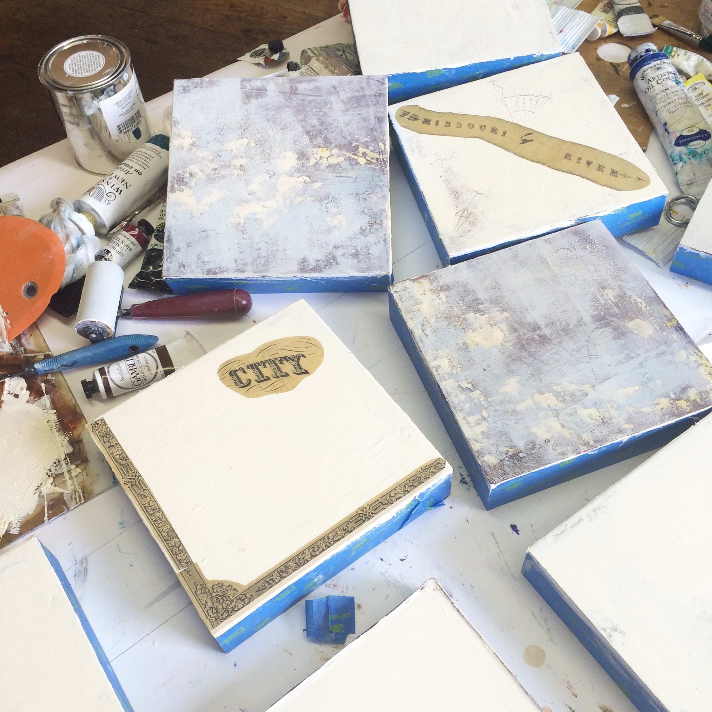 about 10 panels in various stages of layering, collaging and other interventions.