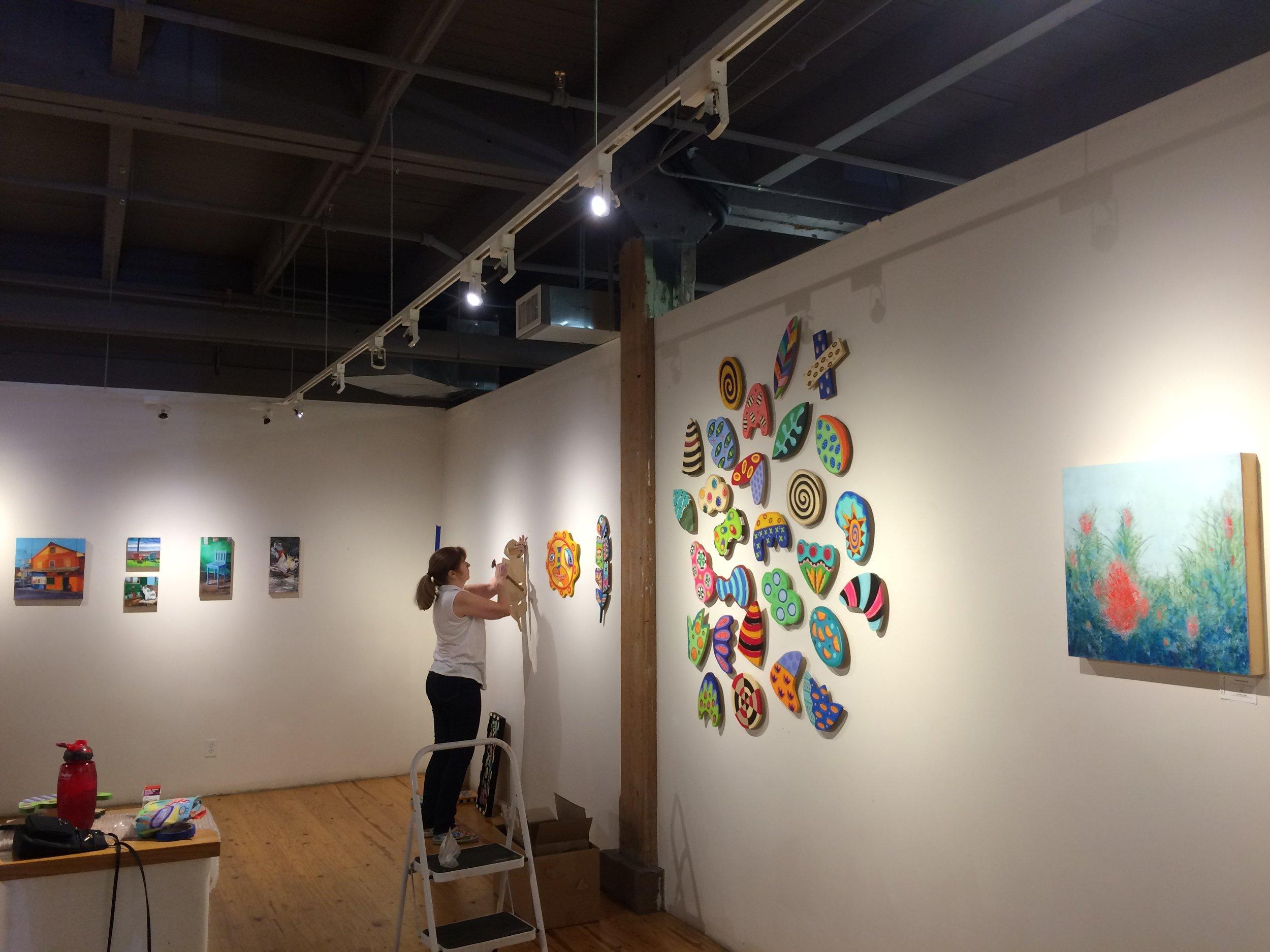 Linda Hatfield hangs her pieces between Katrina's and mine.