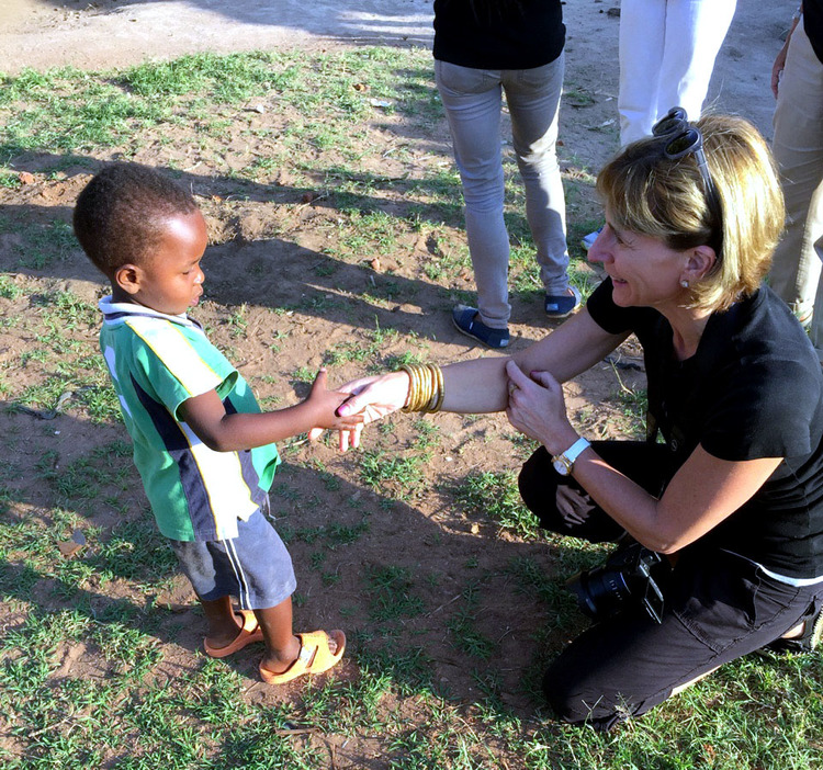 A young Ugandan child meets Paula Resnick during her trip with Innovation Africa.