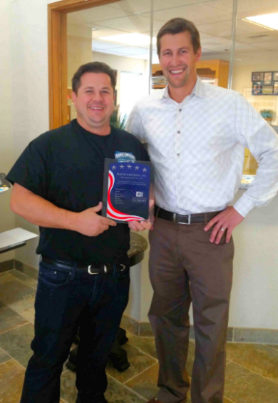 Executive Vice President, Rod Wetherbee, accepting the 2015 Subcontractor of the Year on behalf of Wayne's Roofing, Inc. from Washington Patriot Construction's representative.