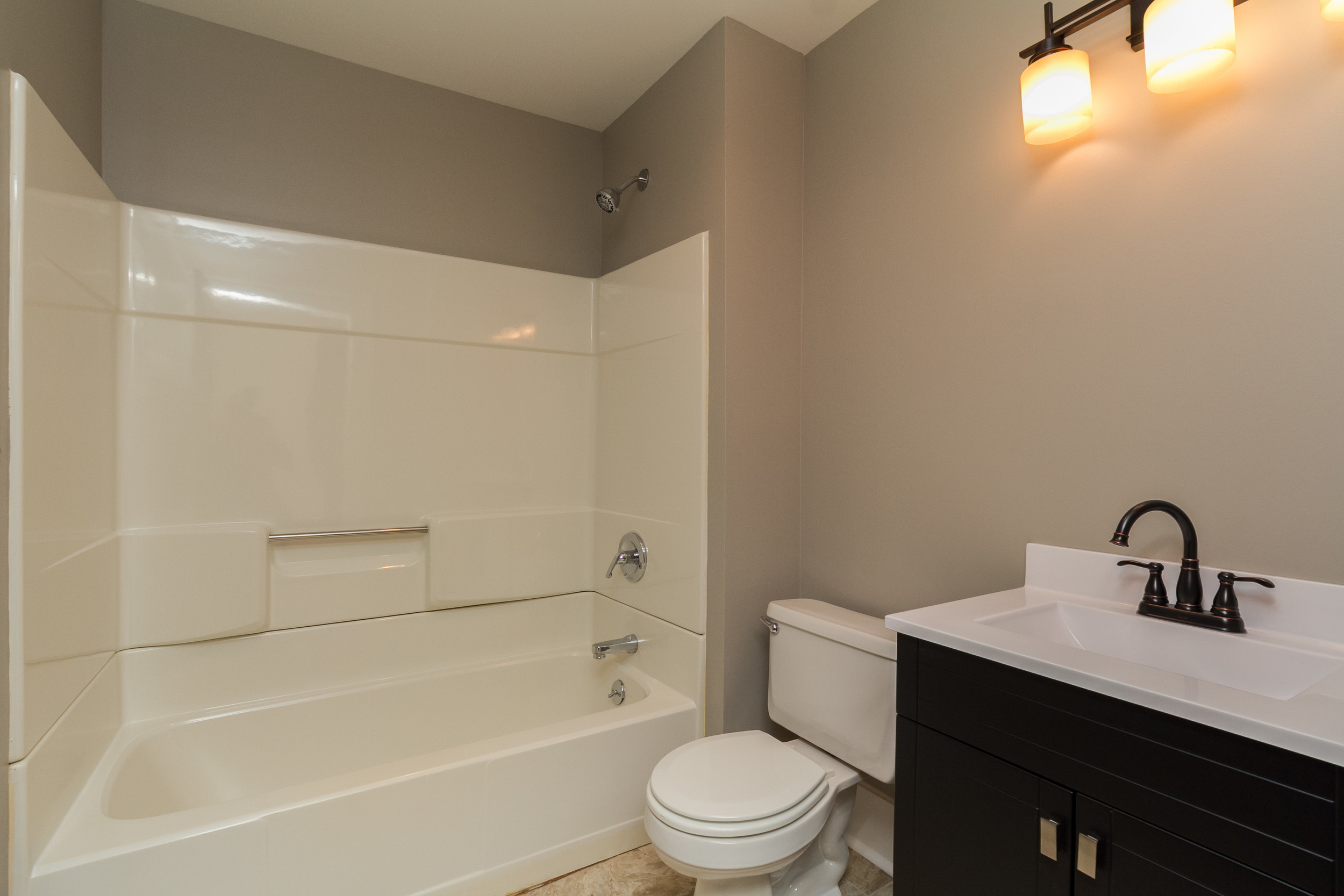 Main bath after - We removed the old tile, added new drywall, vanity, lighting and flooring.