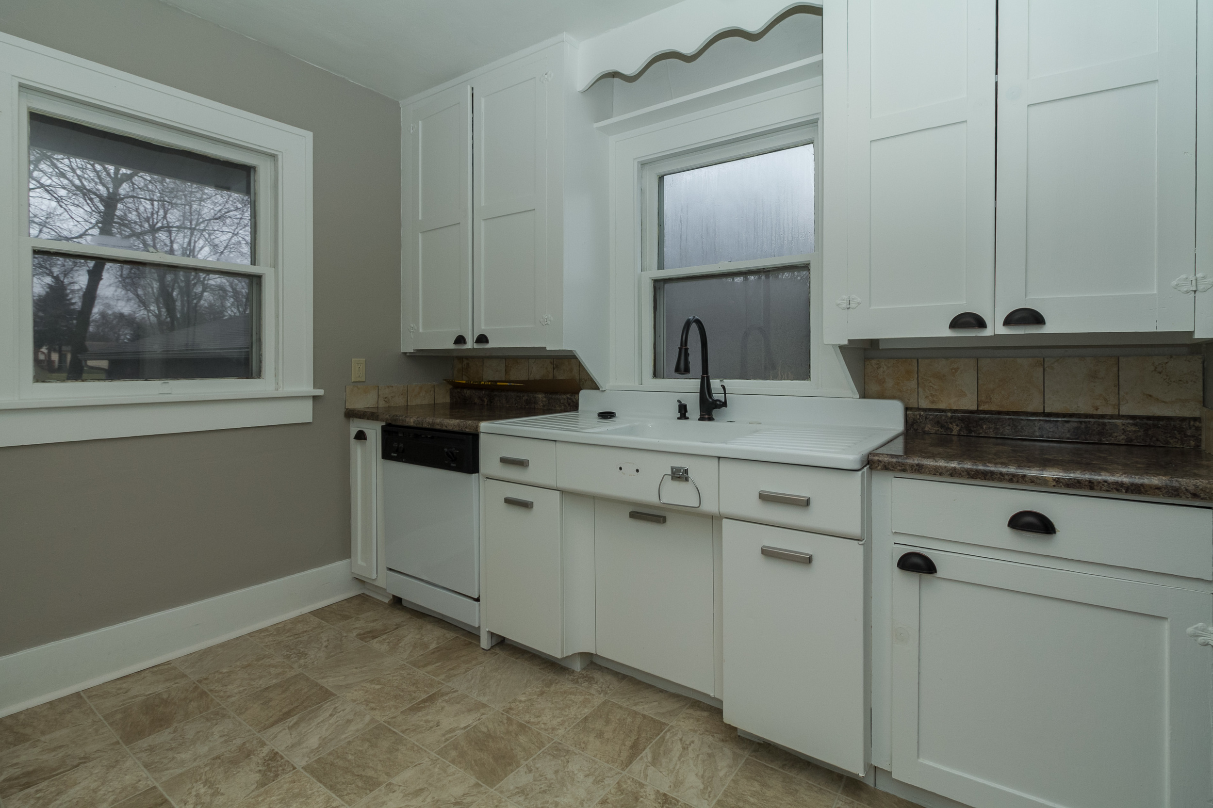 We replaced the countertops, added a dishwasher, hardware, faucet, flooring, painted,and kept the vanity and cabinets.