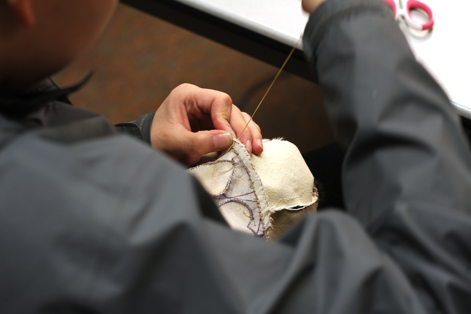 A young woman sews a pair of mukluks, or leather boots, in a traditional sewing class she's taking at the local tribal college. She sews with caribou sinew thread that her grandmother made, an increasingly rare choice.