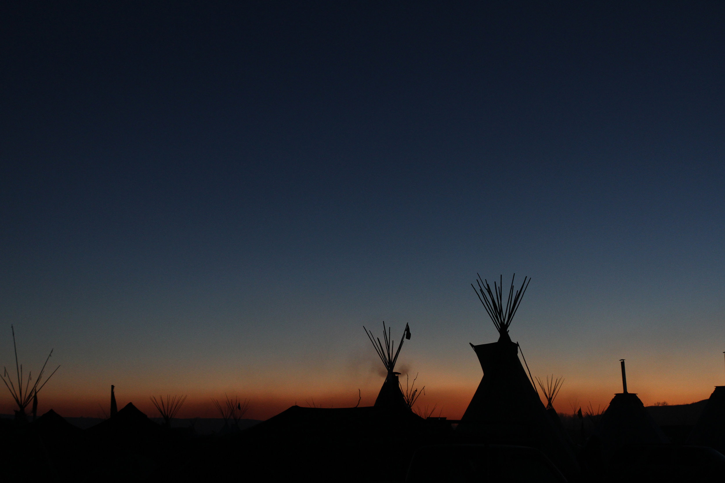 The sun sets behind Oceti Sakowin Camp, the largest of the camps at Standing Rock.