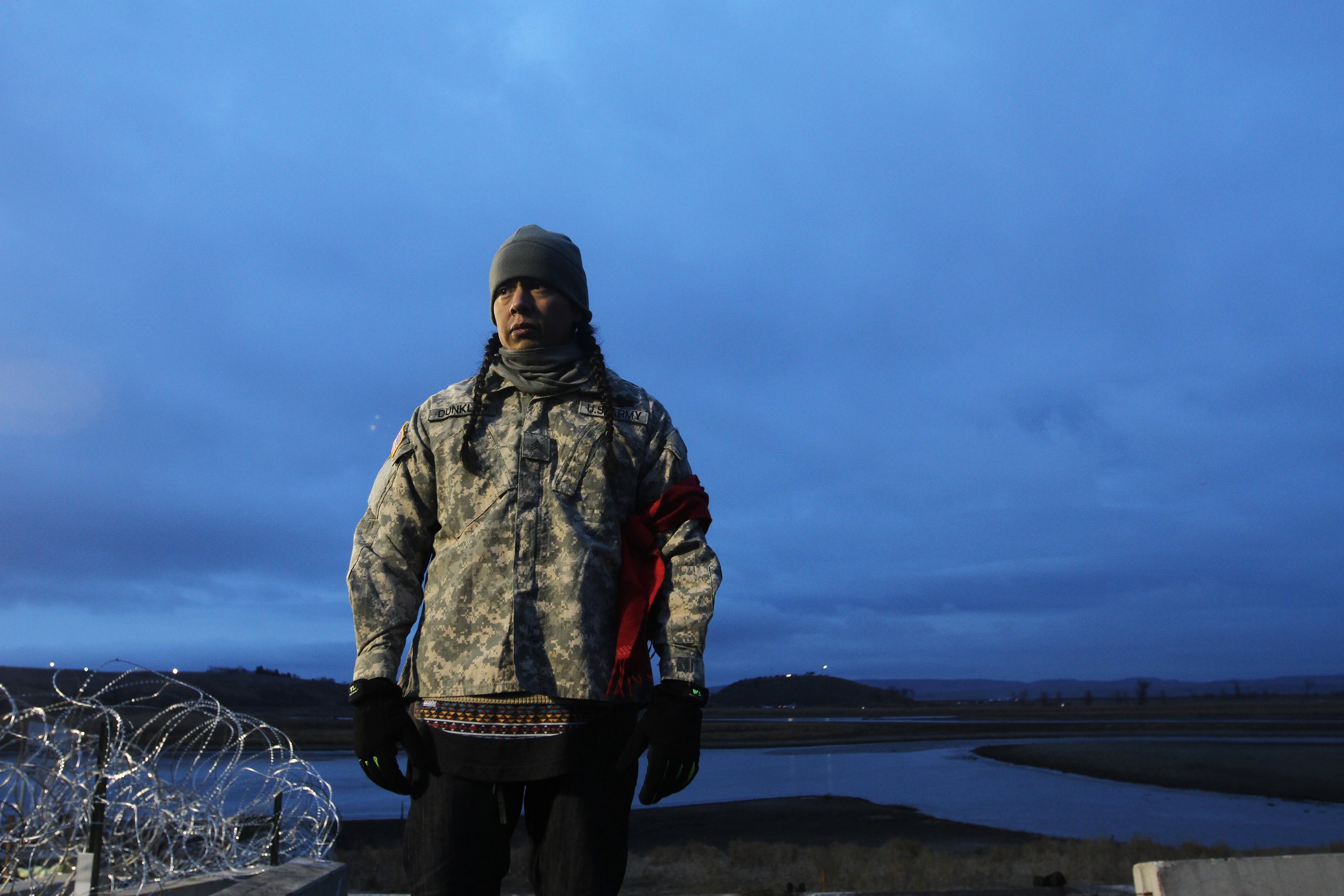 A man overlooks the barbed wire of the police barricade at the Backwater Bridge.