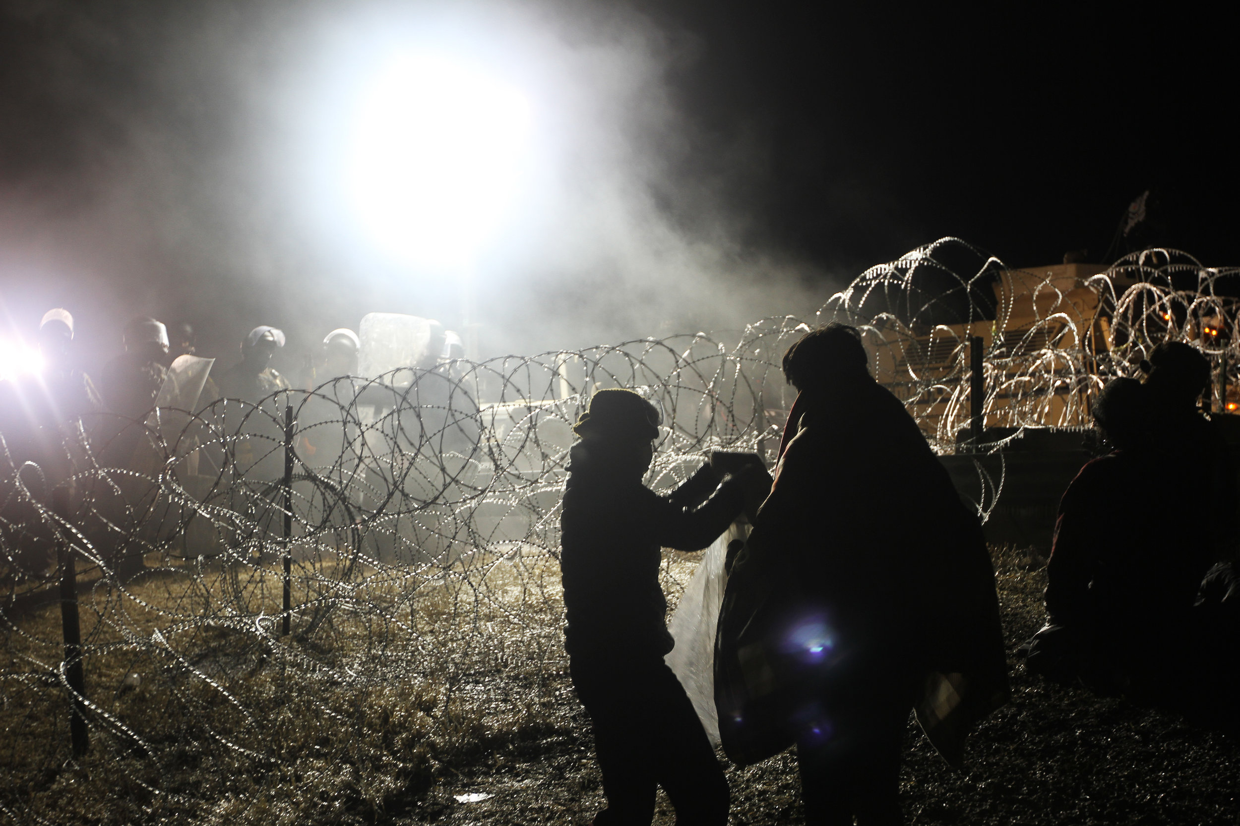 Camp medics worked tirelessly through the night to keep to protestors safe. Here they provide blankets to a man who has been sprayed with water repeatedly at close range in sub zero temperatures. Police stand behind barbed wire in riot gear.
