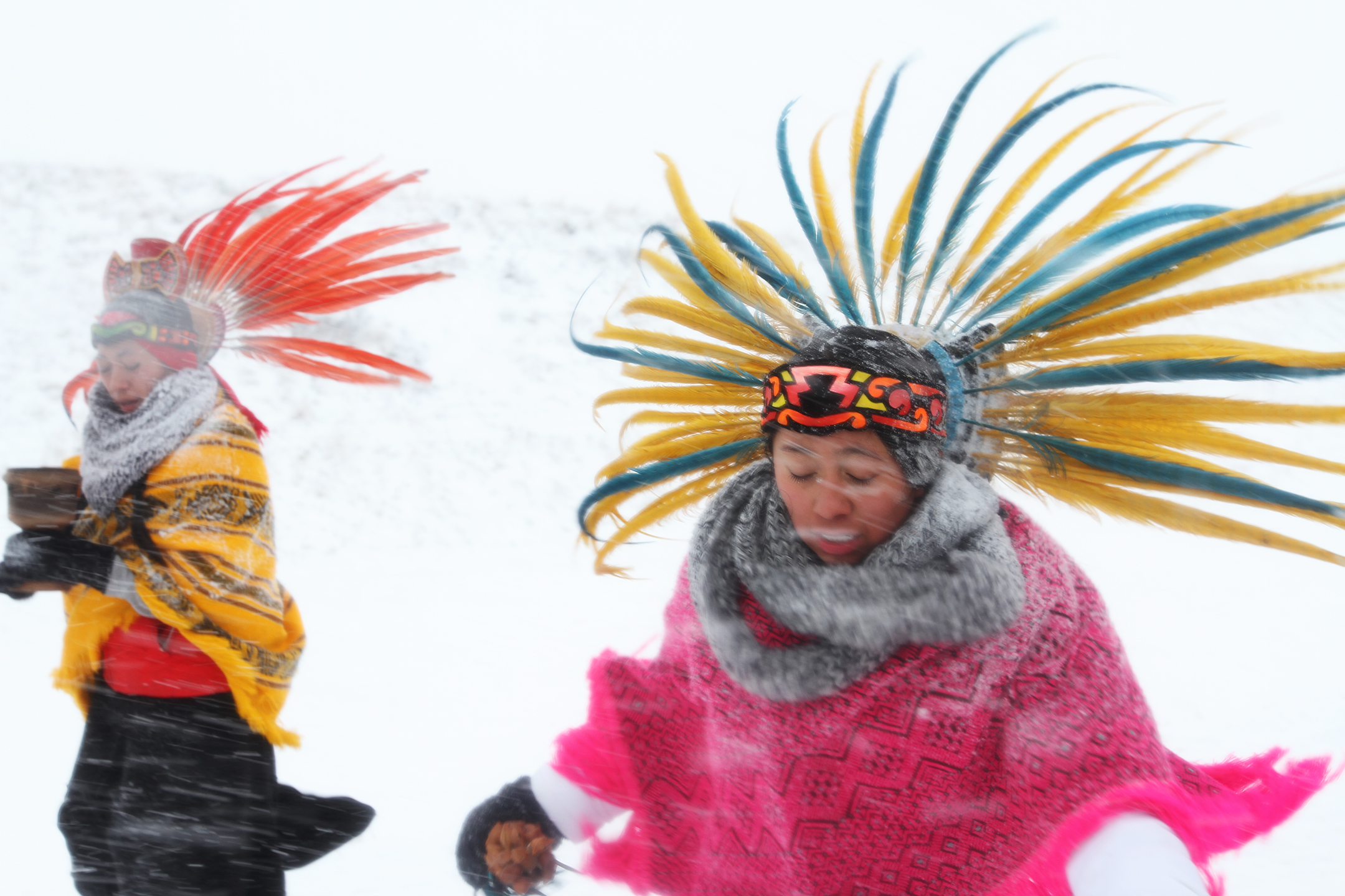 Dancers lead the way to the Backwater Bridge during the Veterans March as the second blizzard of the season moves in quickly.