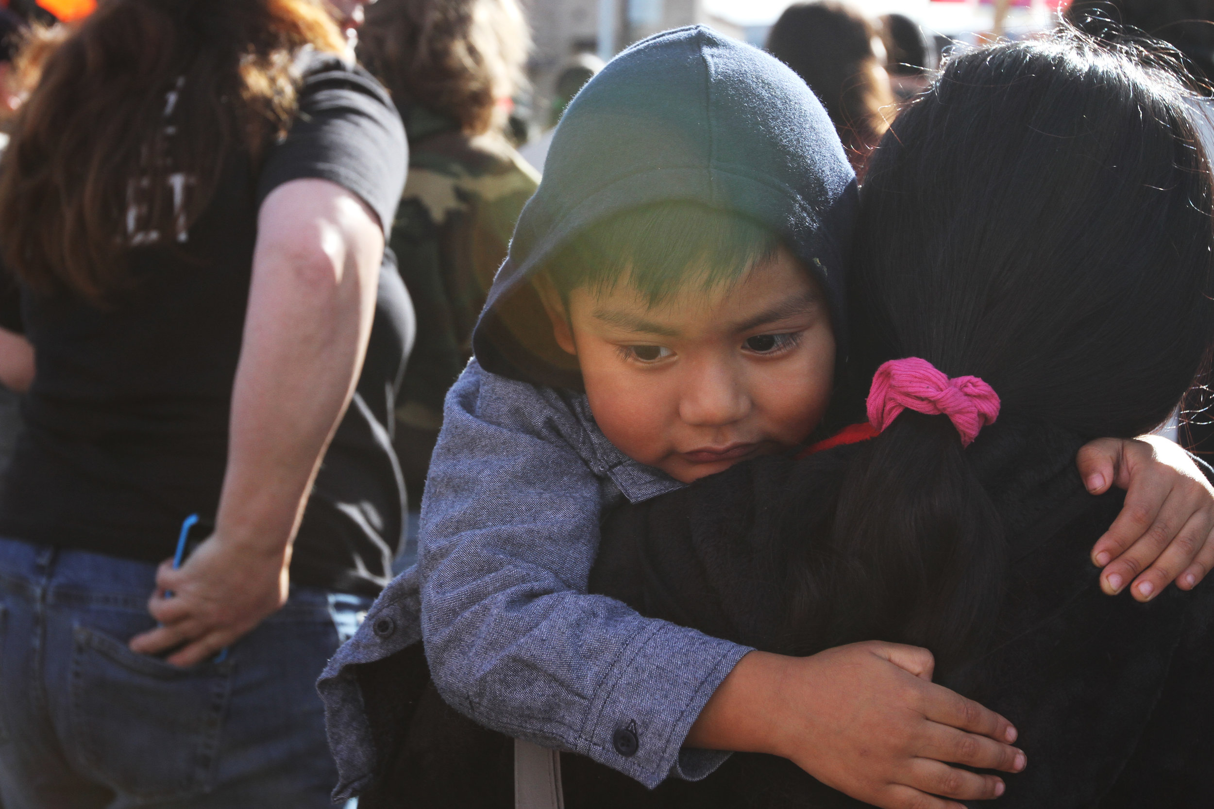 A child gets carried during a seven mile long march advocating for migrant workers.