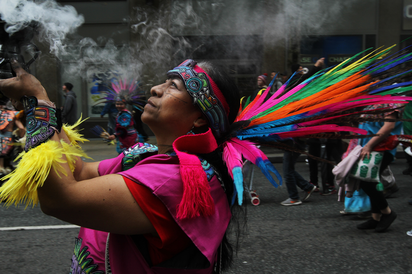 A woman burns ceremonial smoke during a May Day march in Seattle, WA.