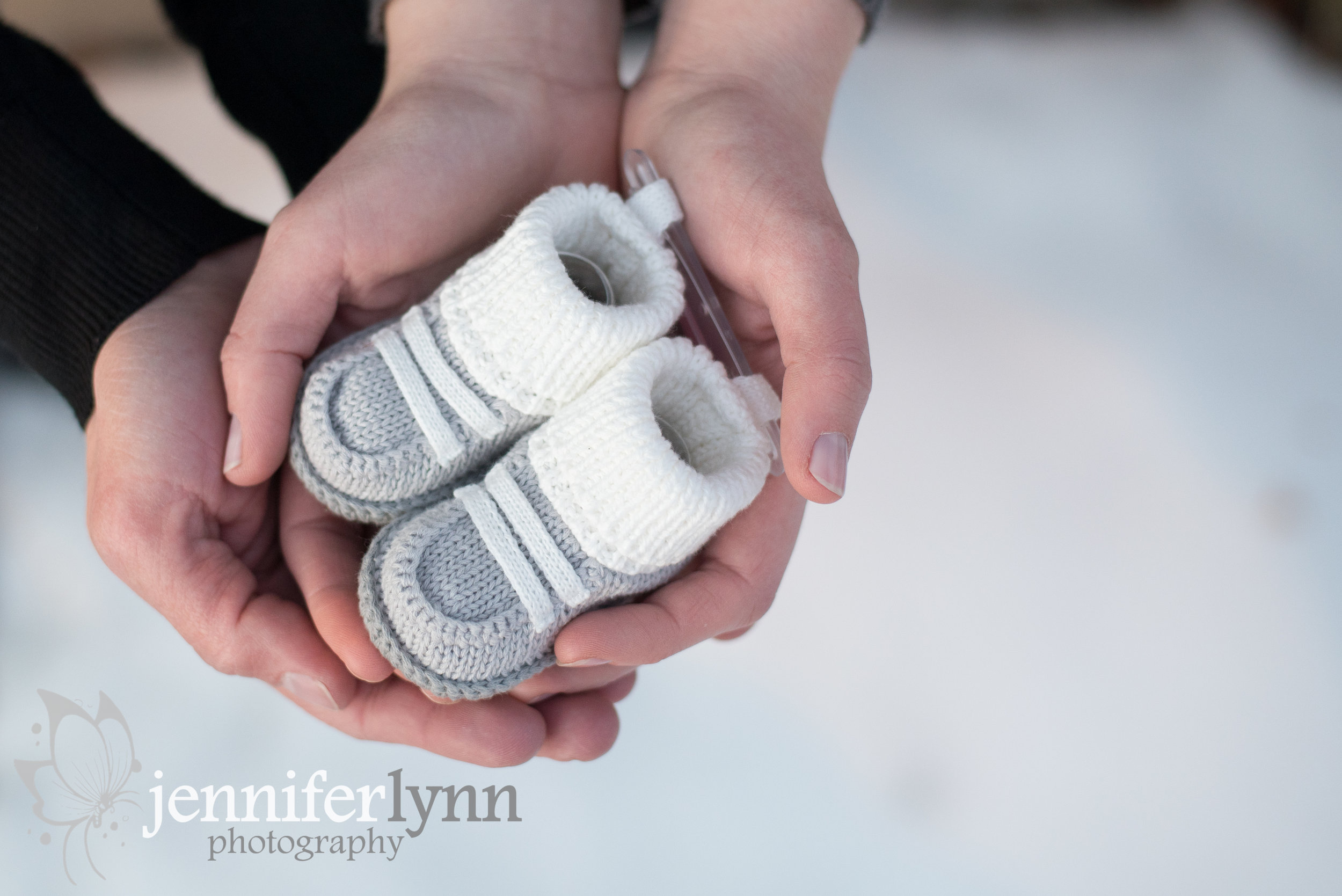 Maternity Hands Holding Baby Booties
