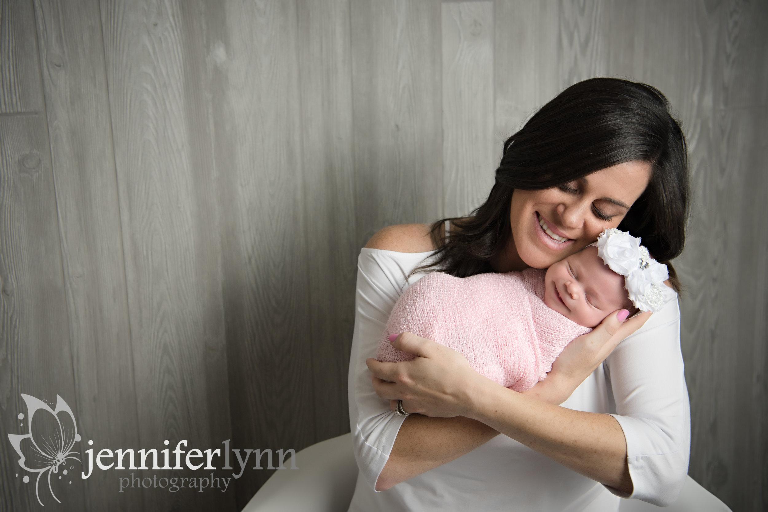 Mom Snuggles Newborn Girl
