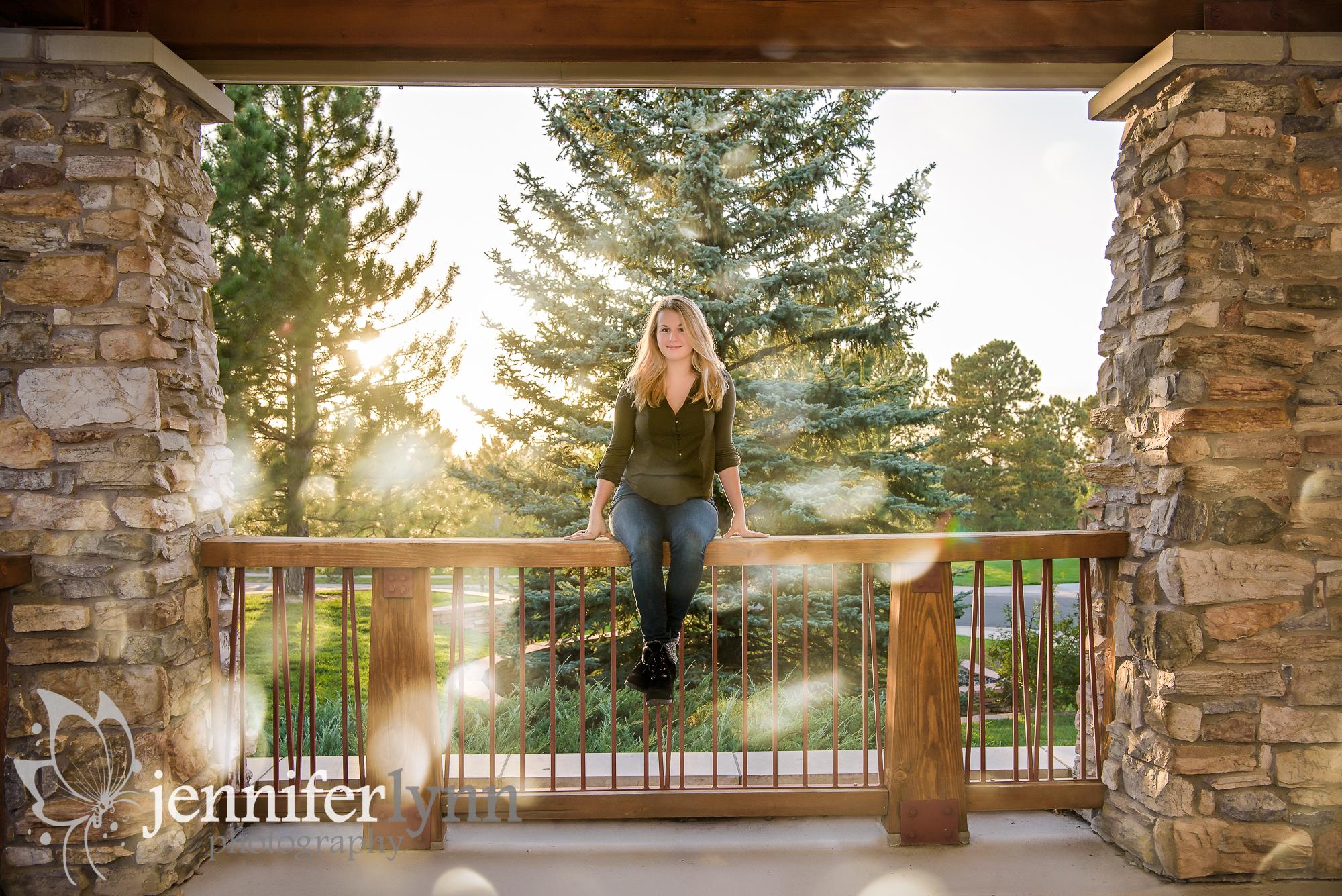 Senior Girl Sits Wooden Railing Sun Streaks