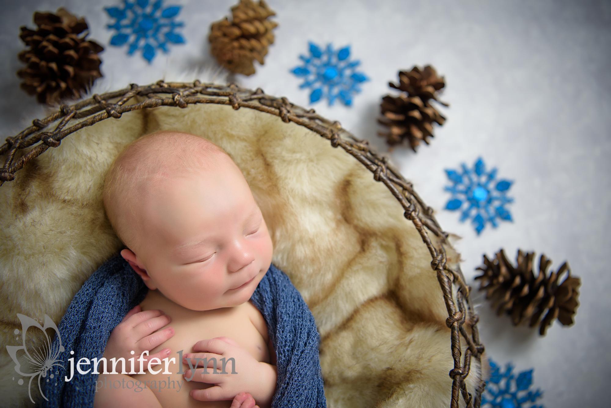 Close up of newborn boy pinecones snowflakes