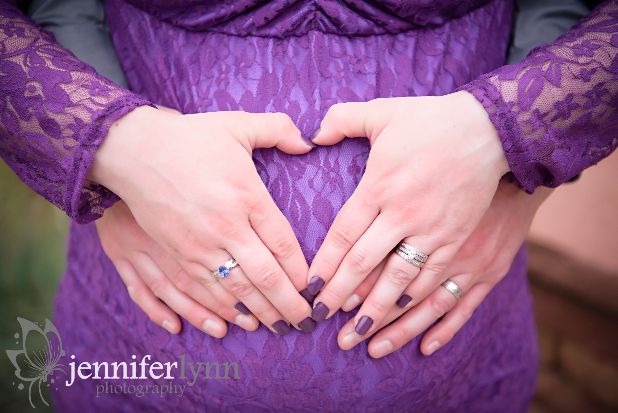 Two hands make a heart on a baby bump
