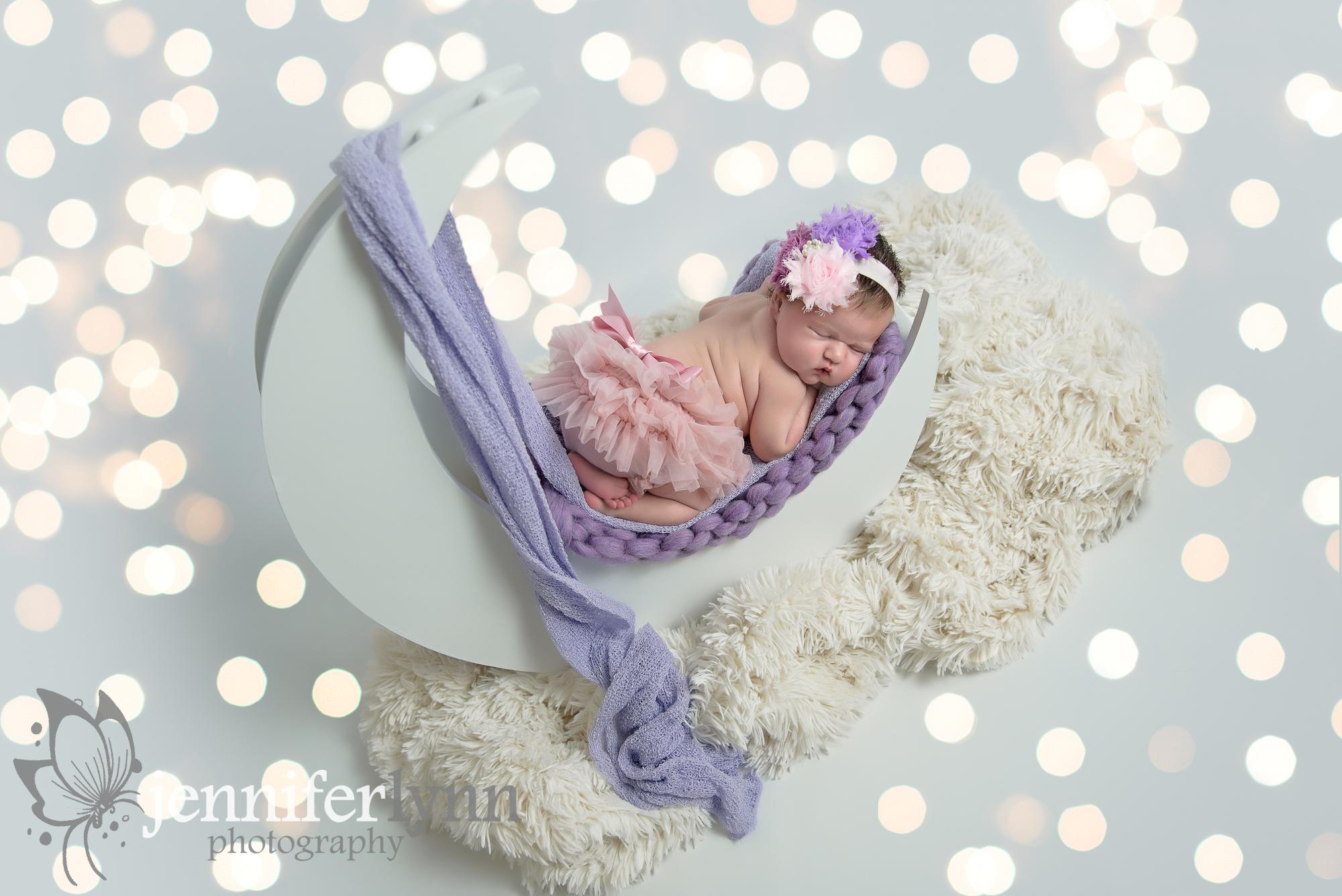 Newborn girl on moon prop with lights