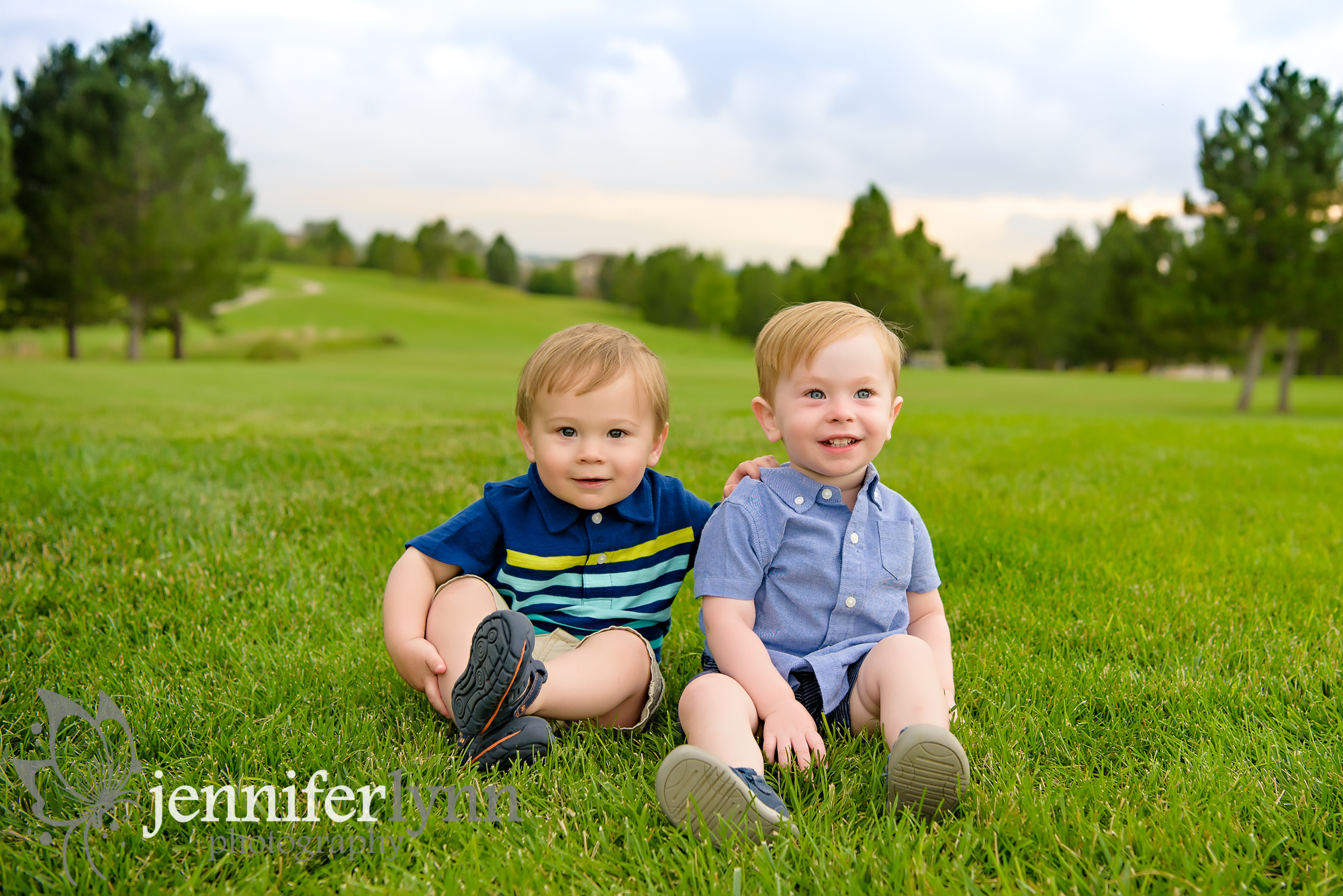 Baby boy cousins sit on grassy area with mountains