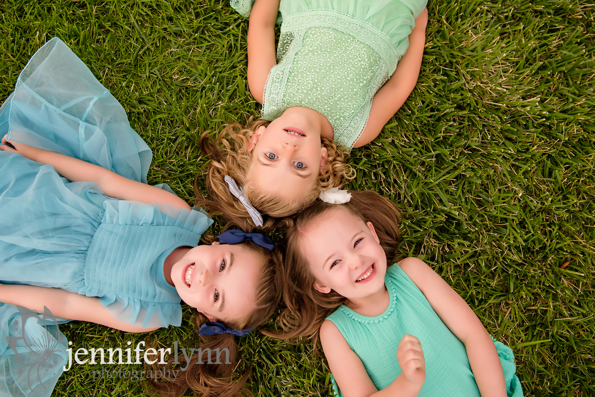 Girl cousins laying on grass looking up