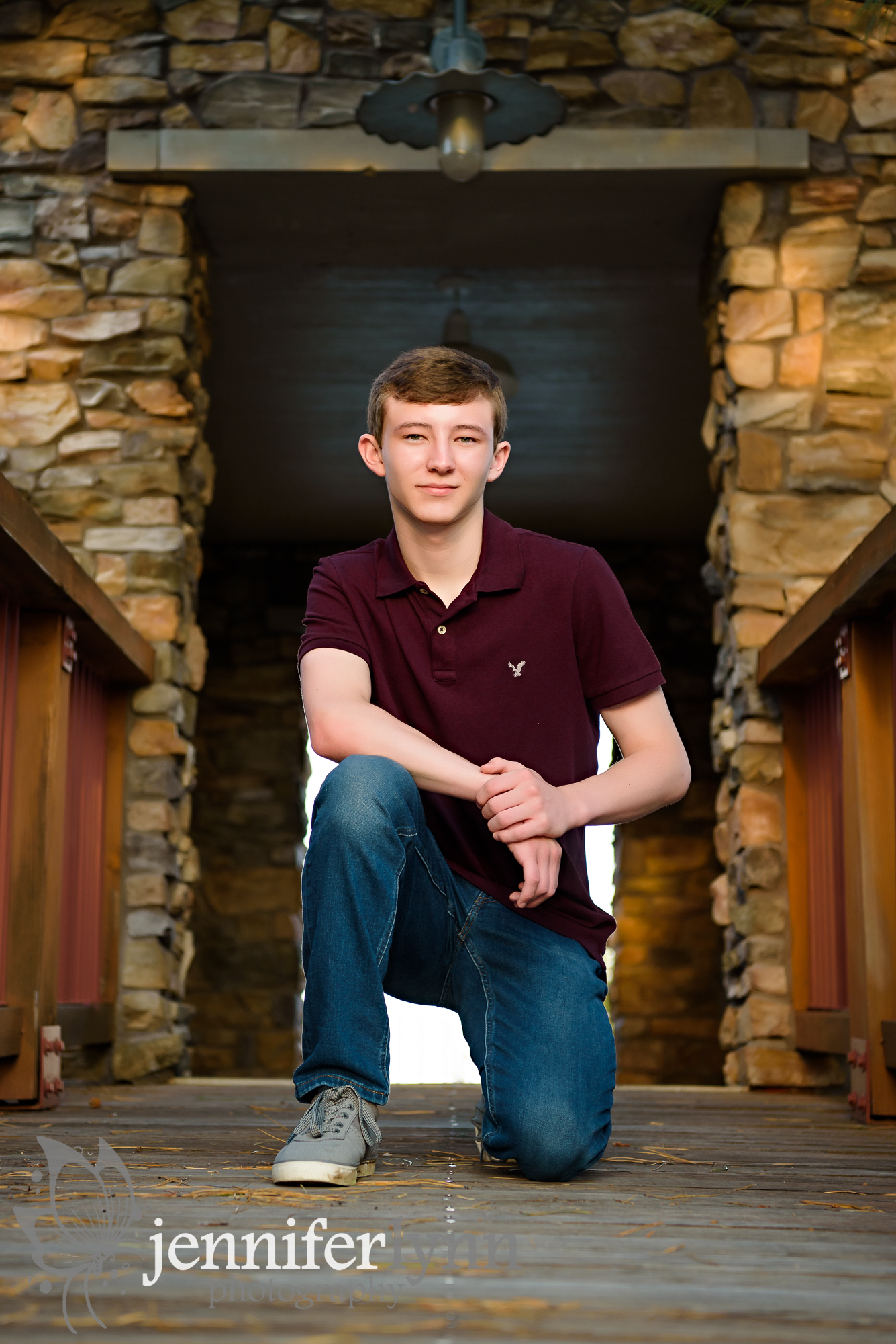 Senior Boy Kneeling on Rustic Bridge
