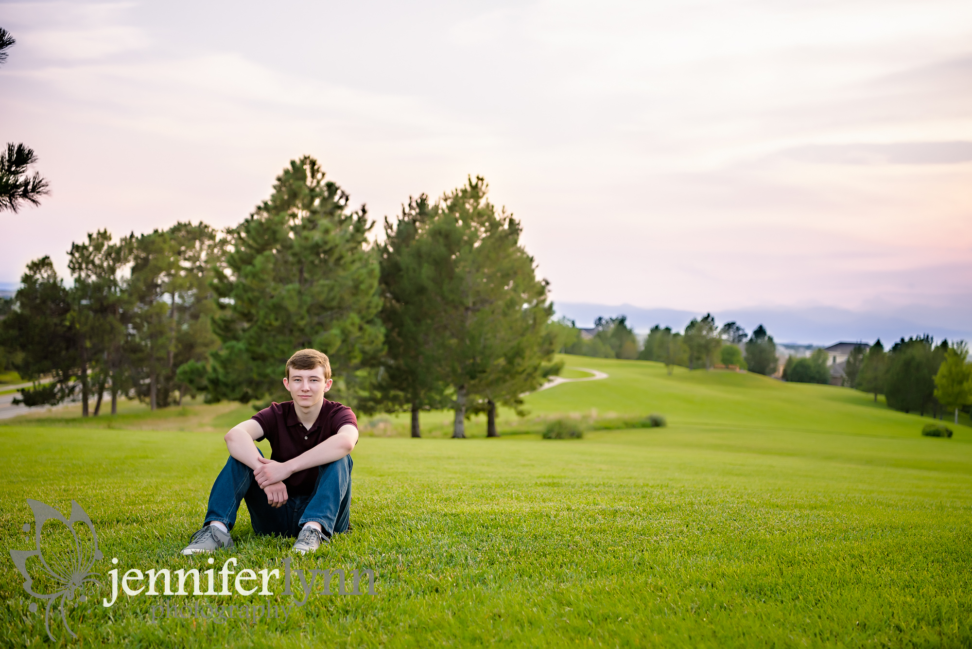 Senior Boy Sitting on Green Hill Mountains Sunset