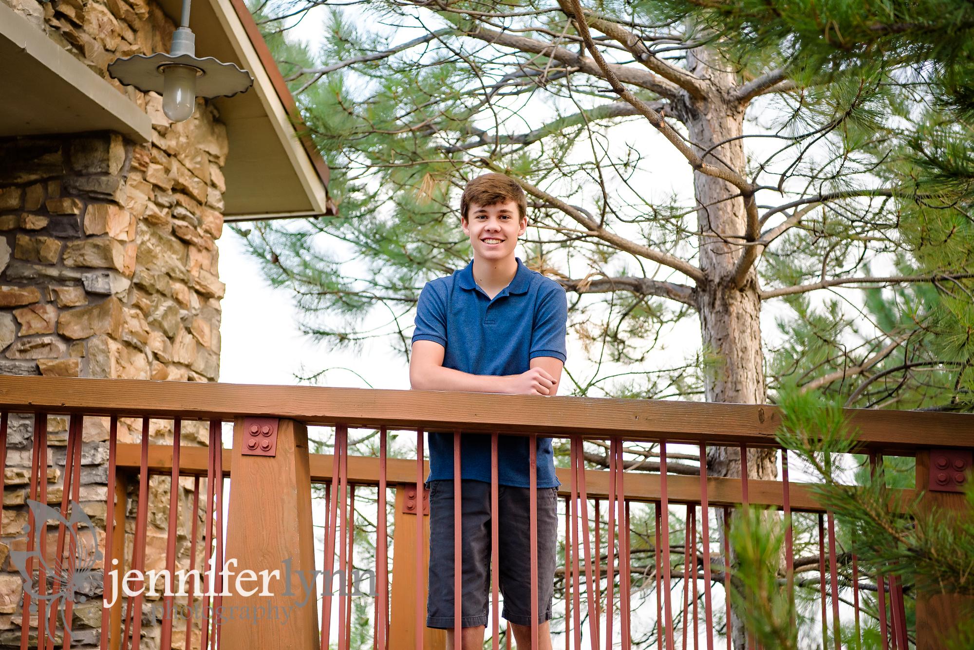 Senior Boy Stands Rustic Bridge