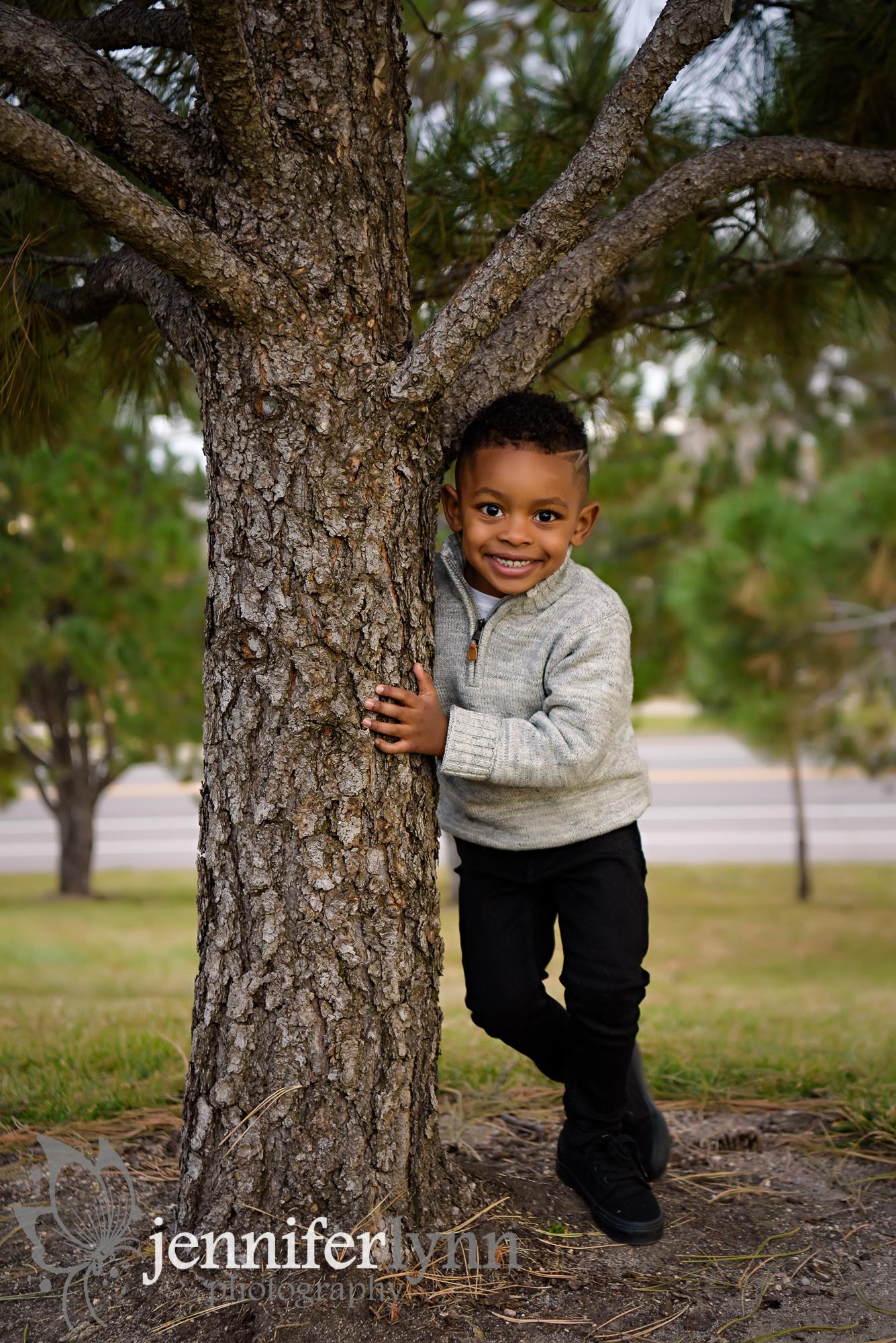 Little Boy Peeking from behind tree