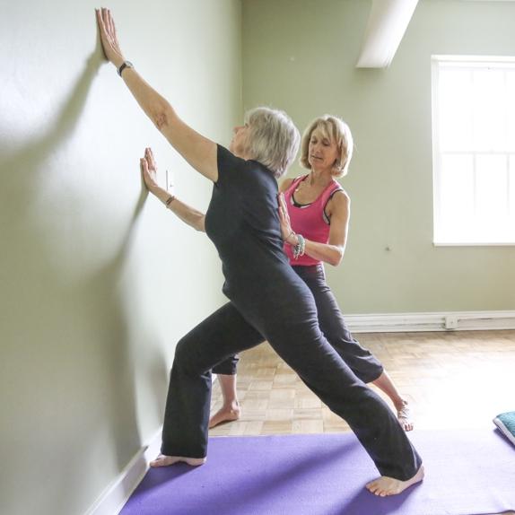 Laura Jane Mellencamp adjusting a yoga student