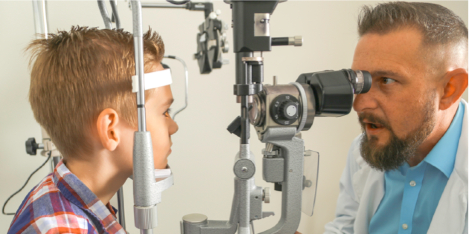 Ophthalmologist examining boy during a comprehensive eye exam.