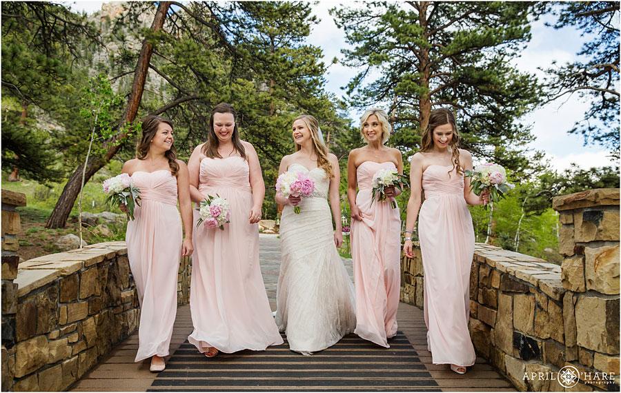 Bridesmaids-Walk-and-Laugh-together-on-the-bridge-at-Della-Terra-Mountain-Chateau-in-Estes-Park-Colorado.jpg