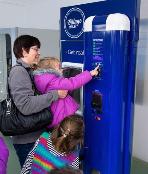 Photo:    A grandmother helping the kids get raw milk from the vending machine