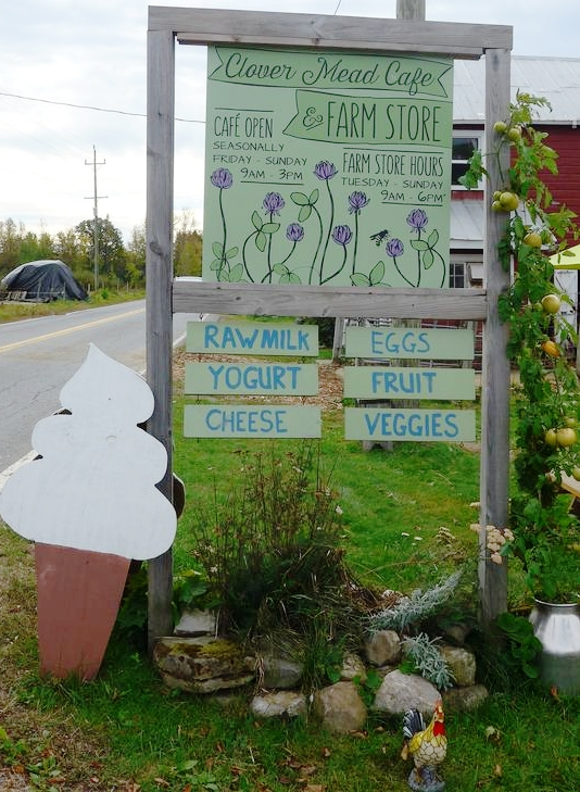 Photo:   the farm's Cafe and farm store road sign where people pick up cheese, yogurt, and fresh, raw milk. It's a community hub for local farmers, friends, and visitors.
