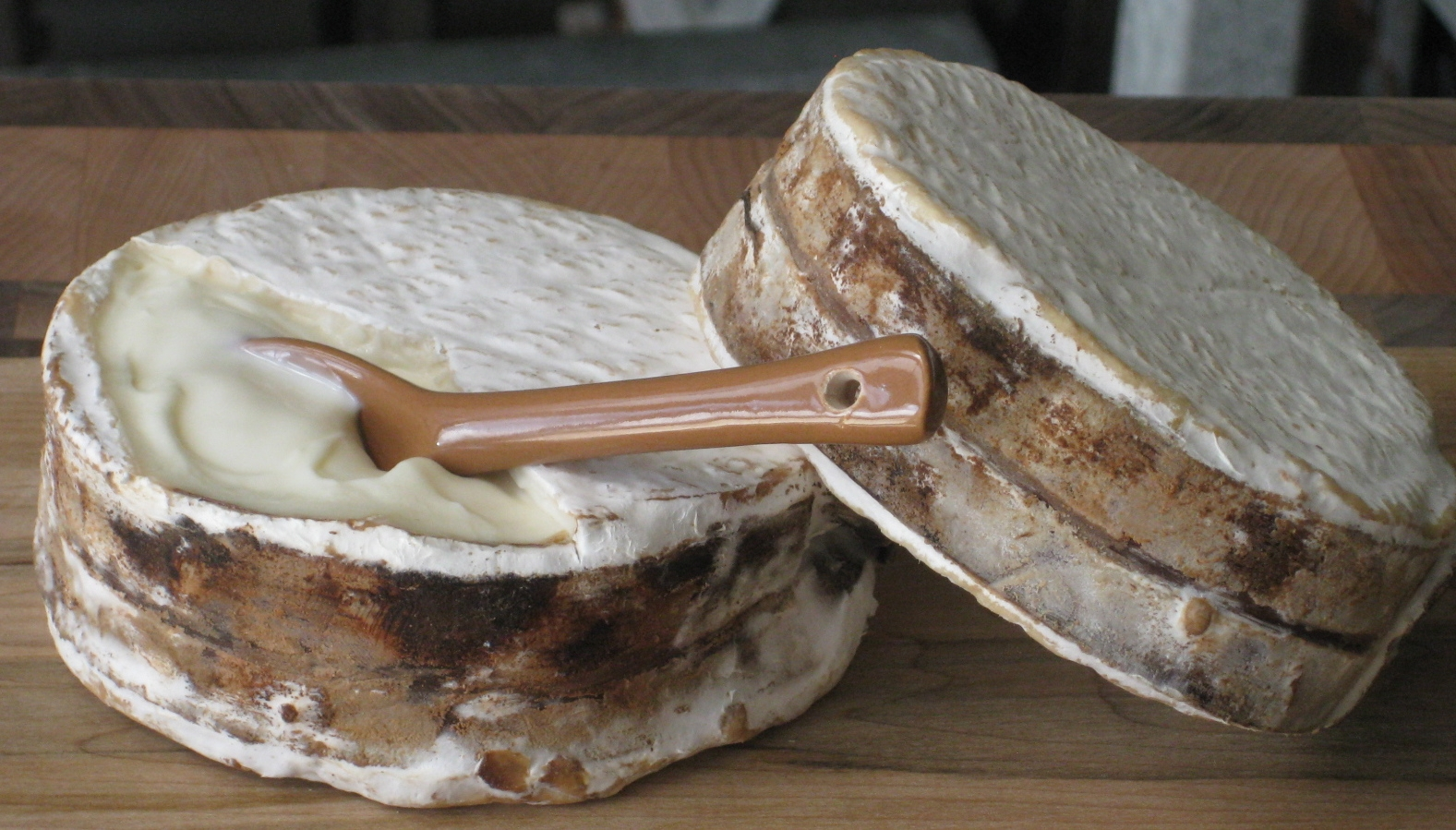 Image:   Jasper Hill Farm's Winnimere raw milk cheese is aged 60 days. Its rind, washed in local beer and bound with a strip of spruce bark, encloses an unctuous, satin interior that harbours scents of fruit and smoke and has mellow richness with tangy undertones of earth. Image via  The Cheese Shop .