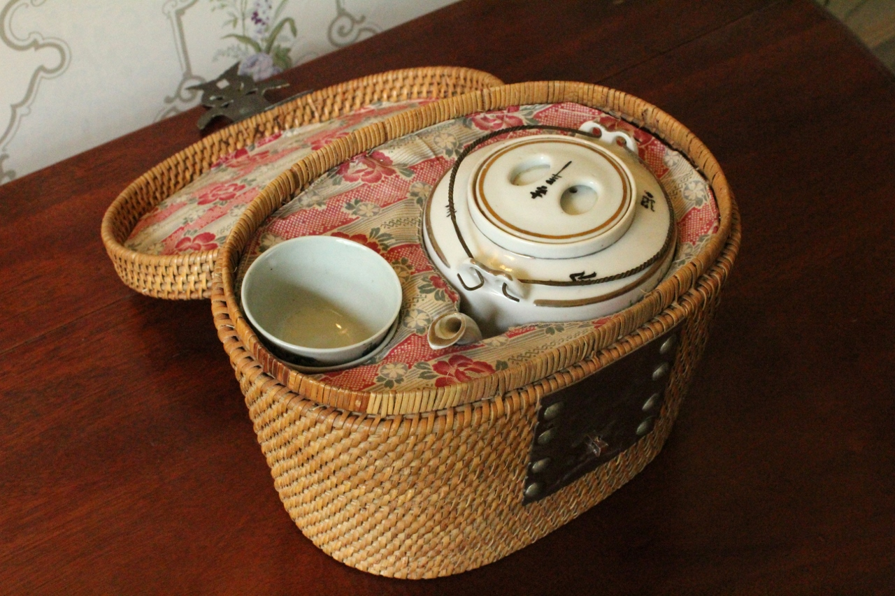Chinese Picnic Basket    Small adoptable, $50 donation   Nestled within this cloth-lined, woven basket rests a teapot and two matching teacups. The teapot depicts two women standing in front of a cherry tree. One woman is holding a branch from the tree, and the other is holding a fan. The front of the basket features a boldly studded metal plate with a decorative fish-shaped hook closure.