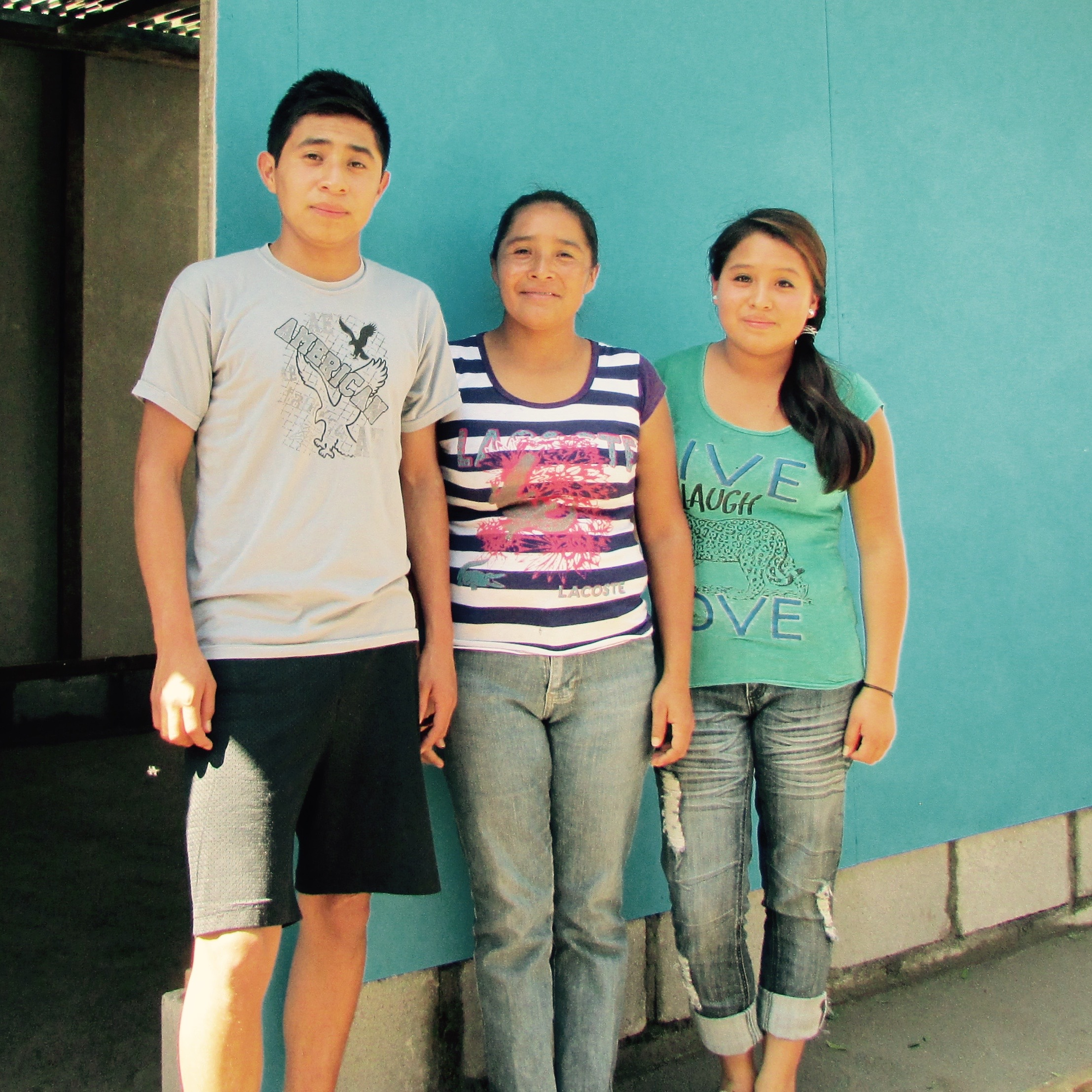 Maria (center) with two of her children. Pictured in front of their new home