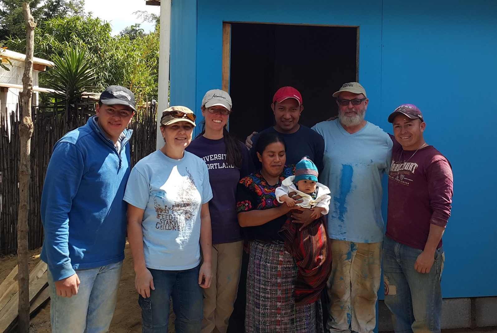 Volunteers and builders with Madelin and her mom outside new home