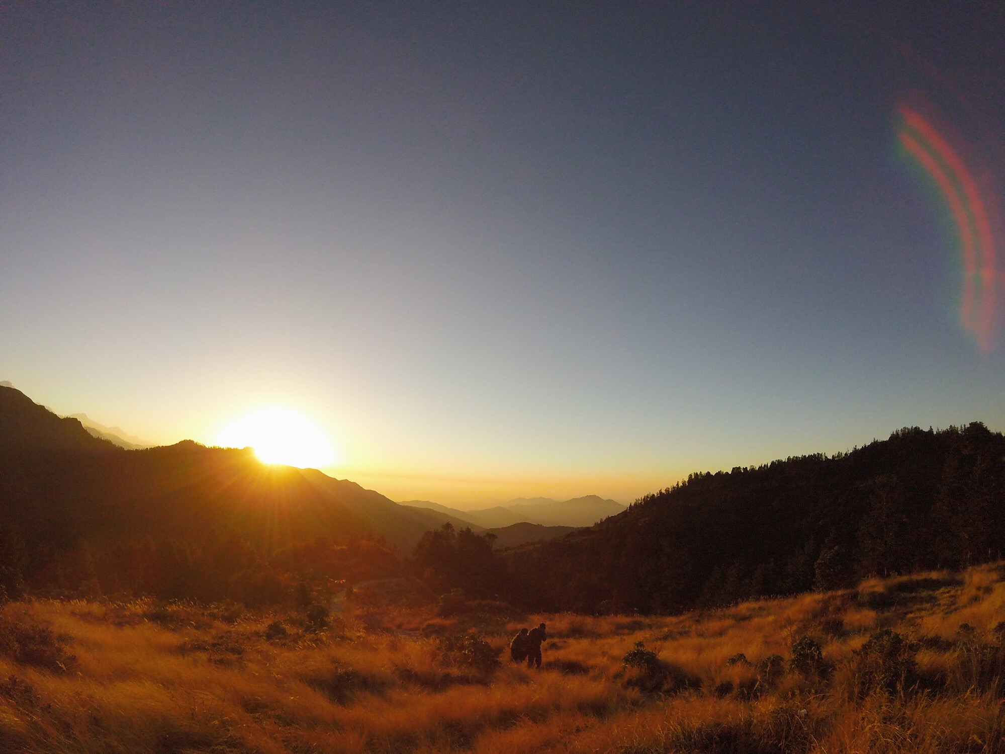 Nov 9.2, 2016   Sun breaks over the eastern edge of the Annapurna Massif lighting the high grasslands to a golden blaze. Pilgrims forge towards the hilltop in short, broken steps over broken shale.