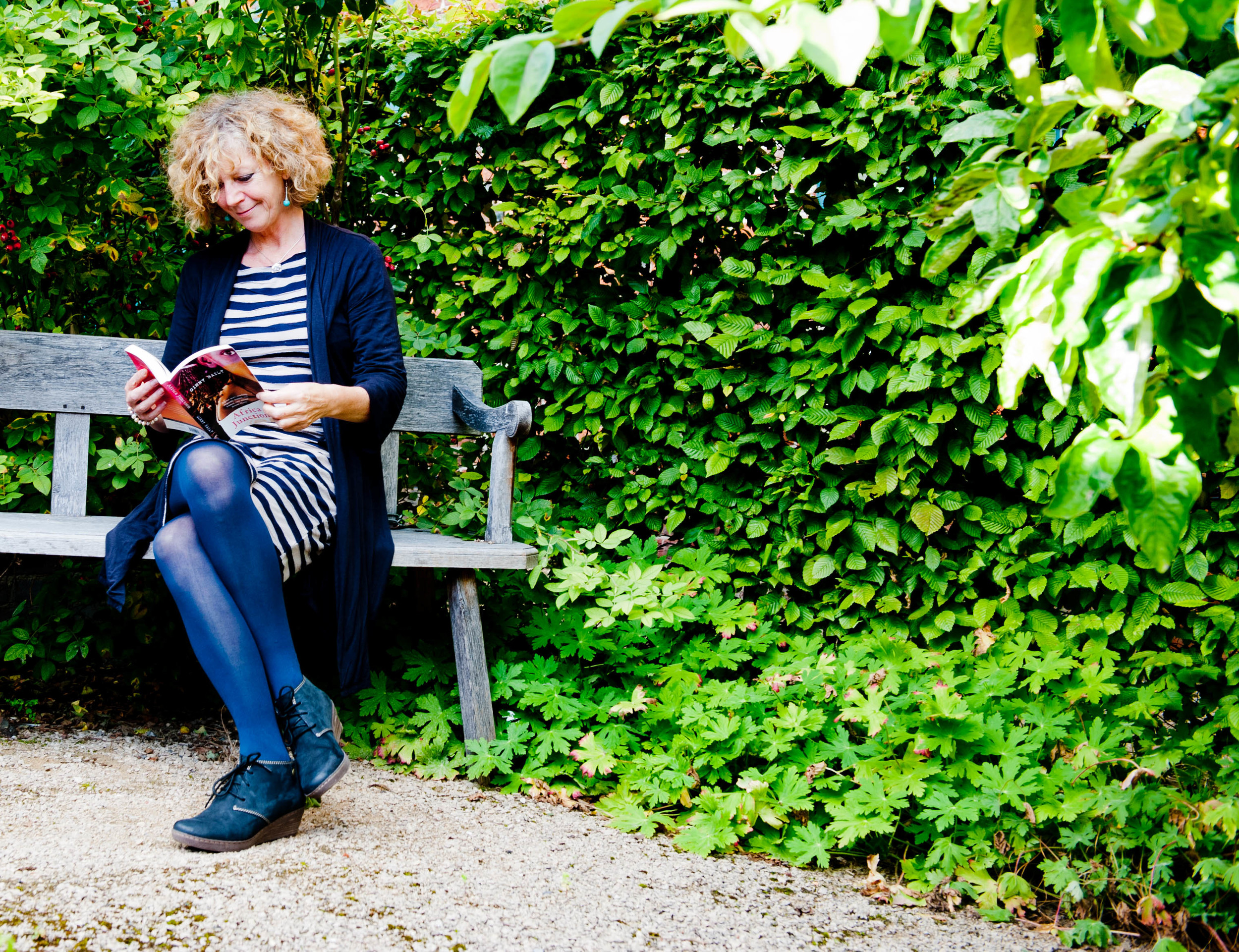 A photograph of the author Virginia Baily sitting on a park bench reading the novel Africa Junction