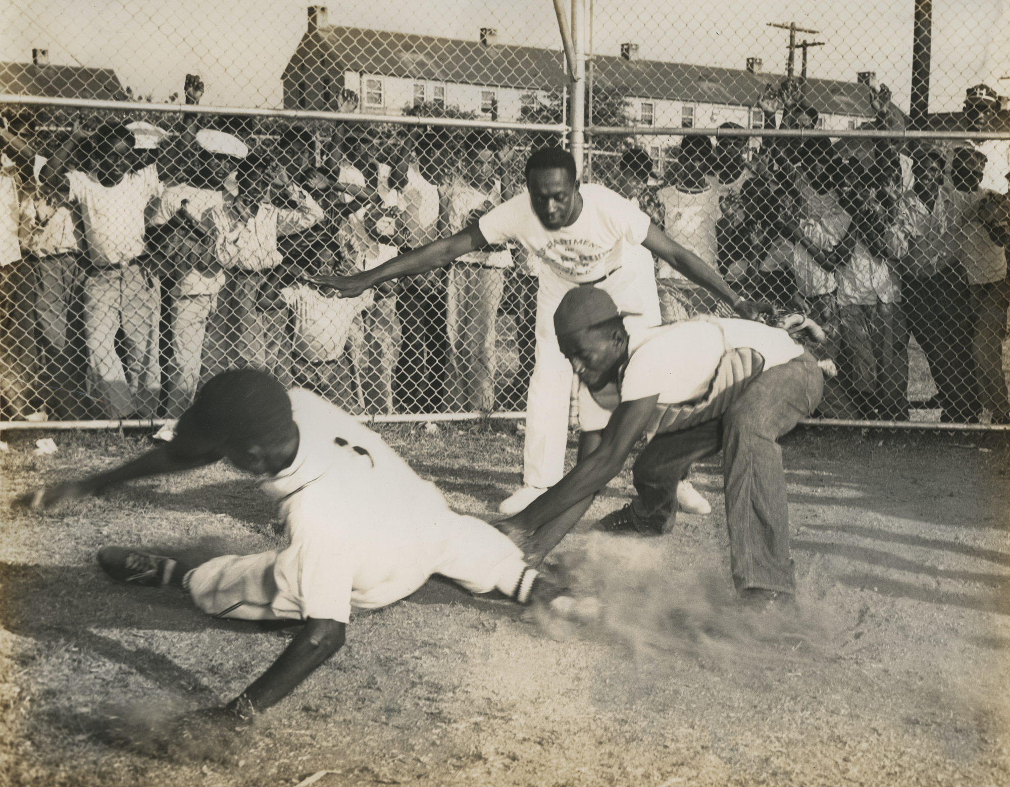 "Baseball player sliding into home plate with umpire signalling ""safe."" New Orleans (La.) Recreation Dept. Scrapbook photographs, 1947-1948"