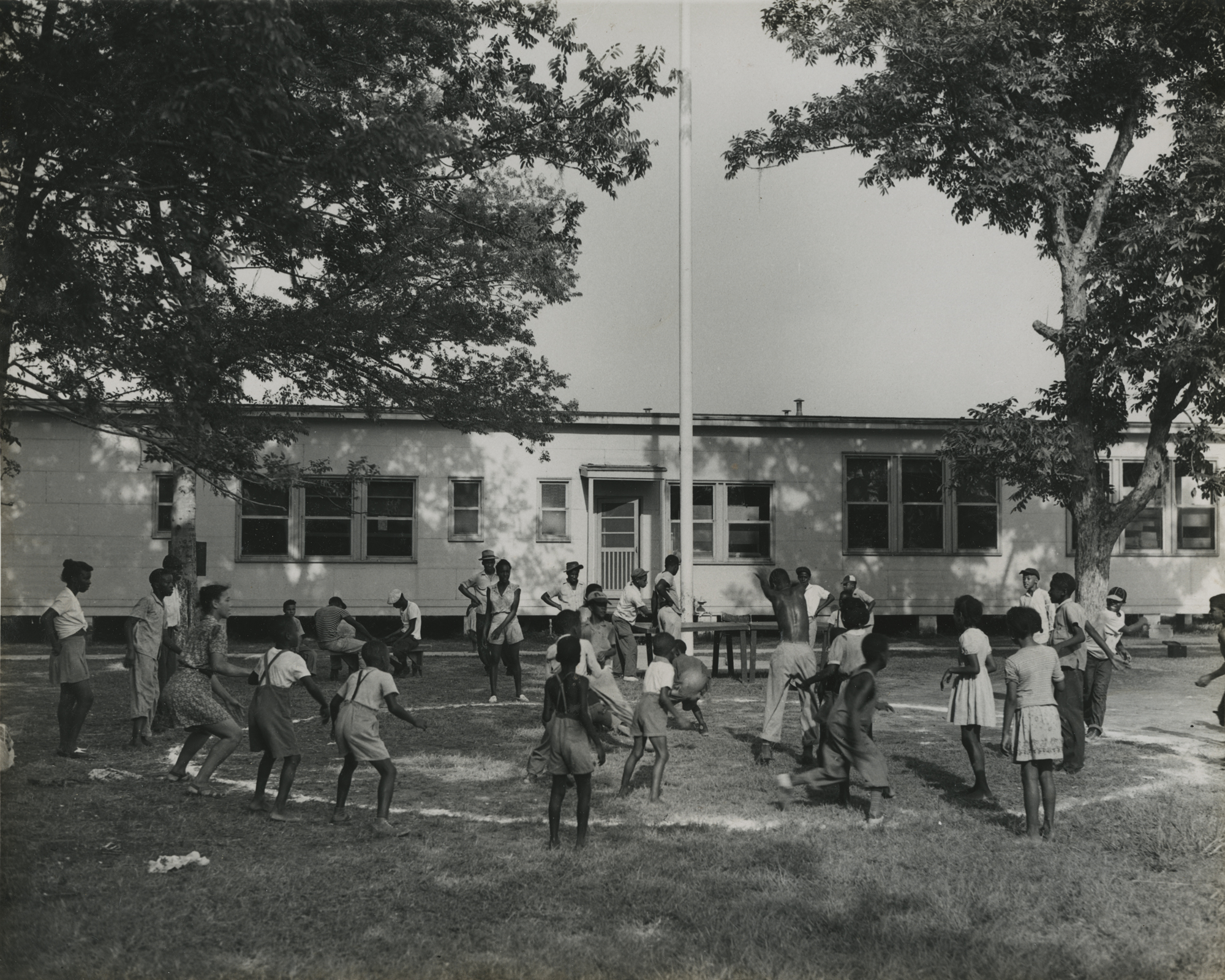 Children playing in a circle in front of a building. New Orleans (La.) Recreation Dept. Scrapbook photographs, 1947-1948