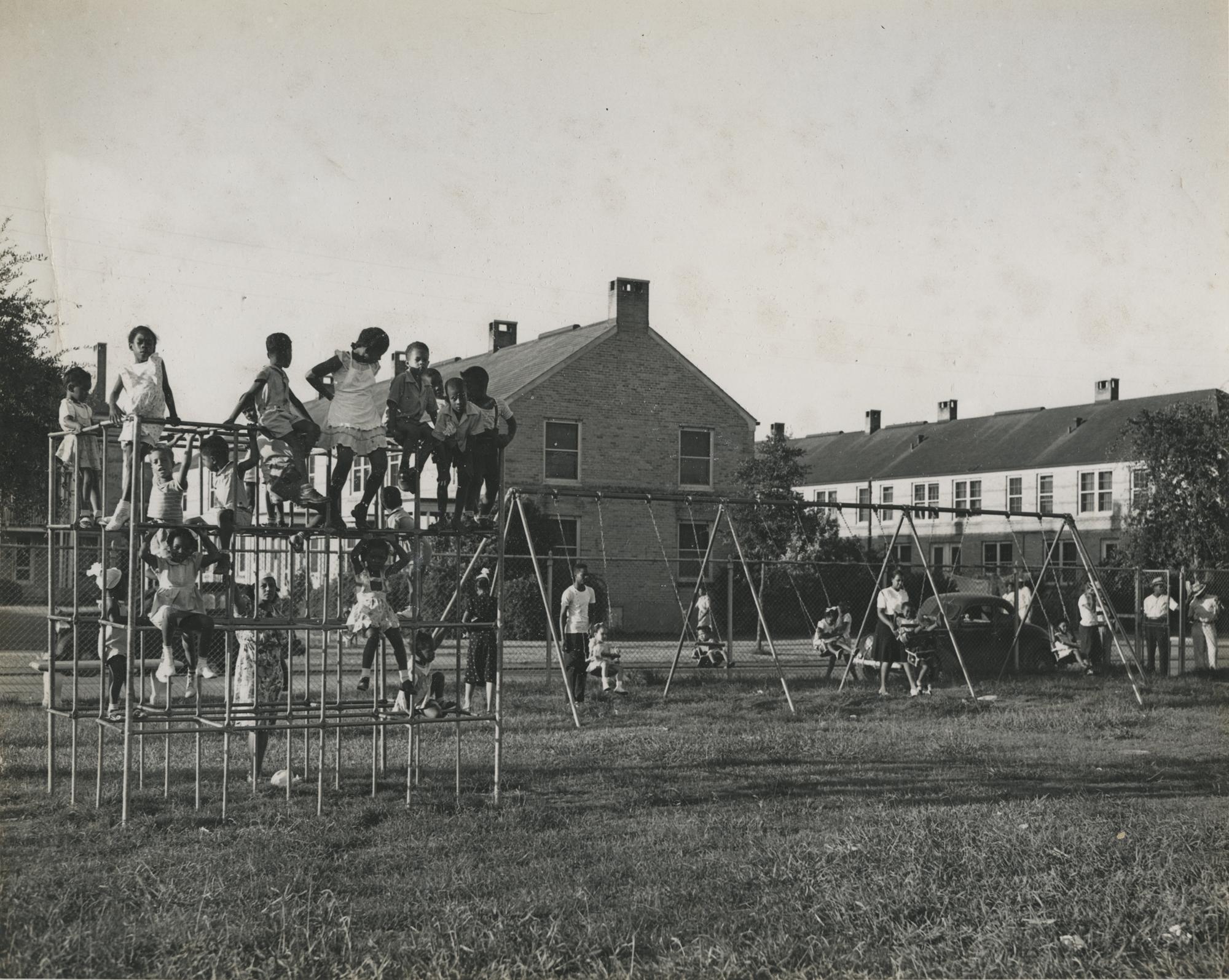 Children on playground equipment at Lincoln Playground. New Orleans (La.) Recreation Dept. Scrapbook photographs, 1947-1948