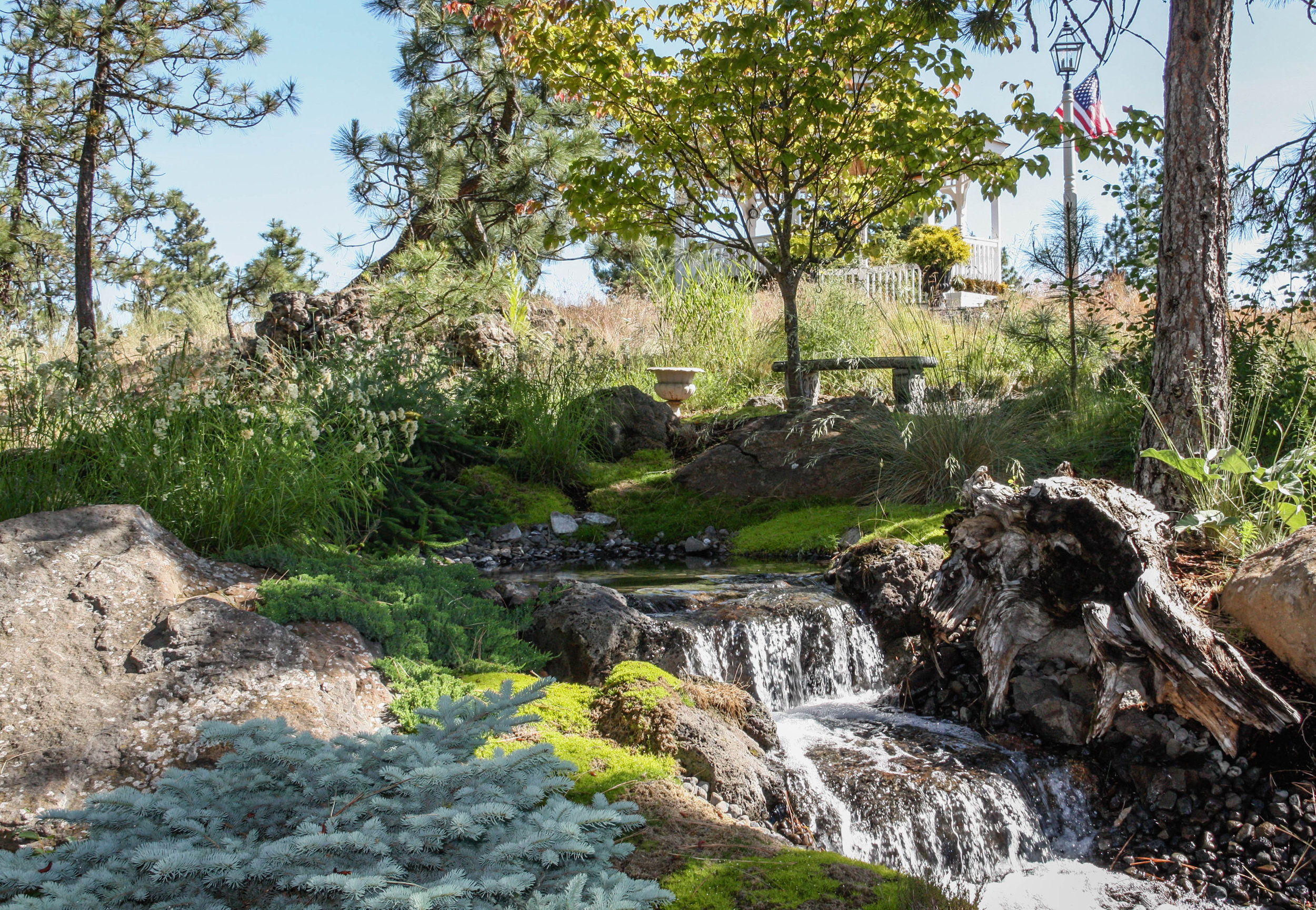 sitting area by natural stream water feature spokane landscape