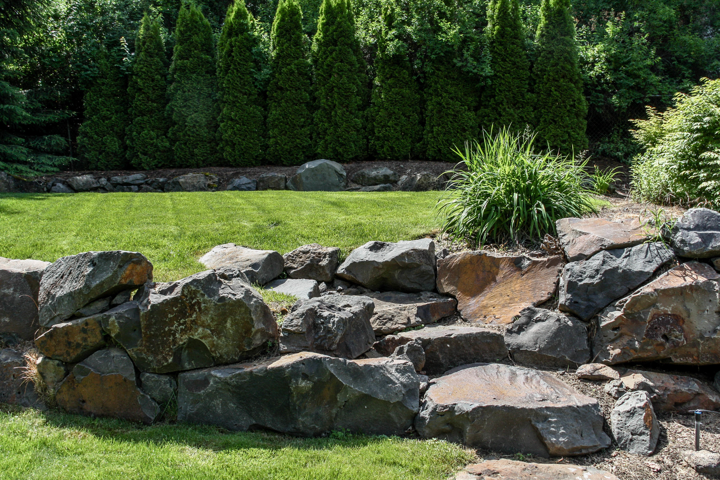 basalt boulder retaining wall with stone steps on spokane south hill
