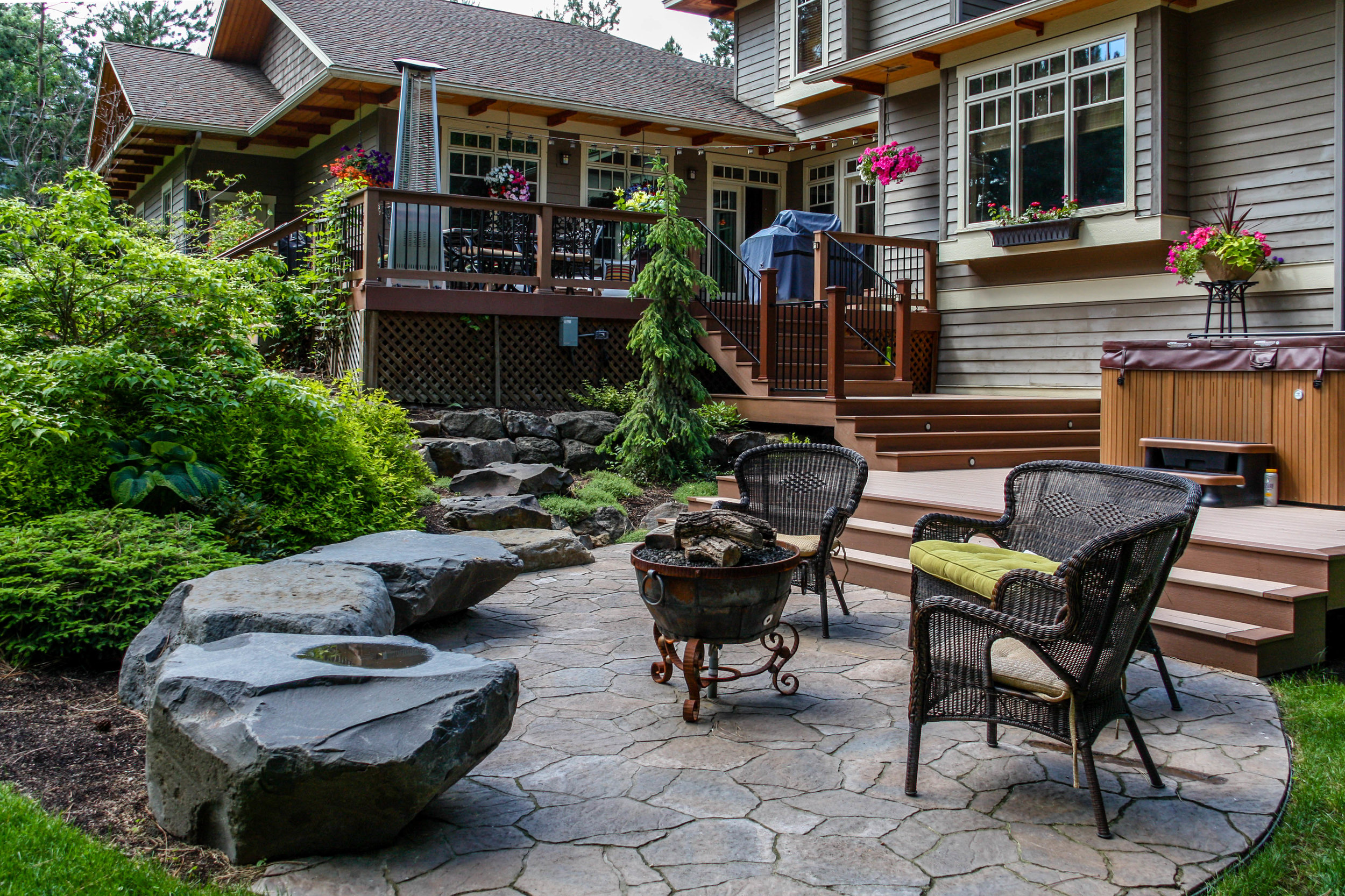 paver patio and bench rocks off of multi level deck