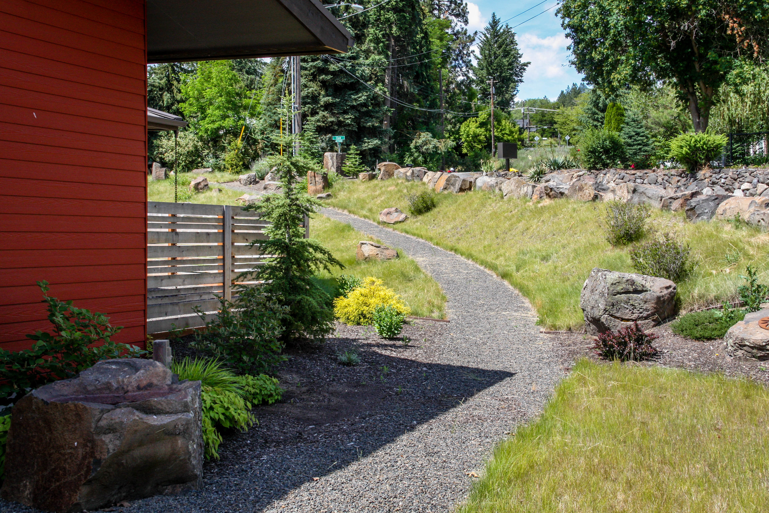 gravel pathway on hillside and horizontal wood fence