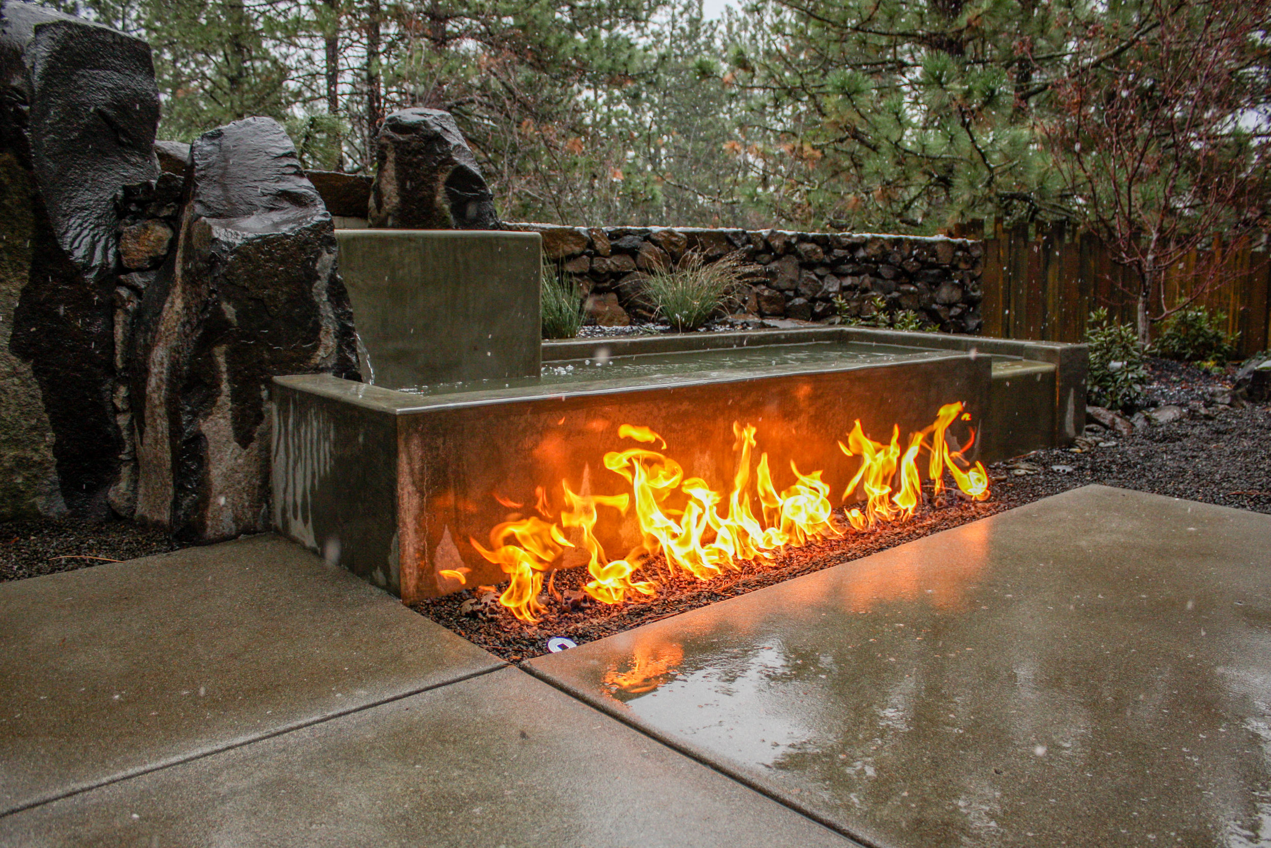concrete and basalt column water feature with in ground gas fire pit