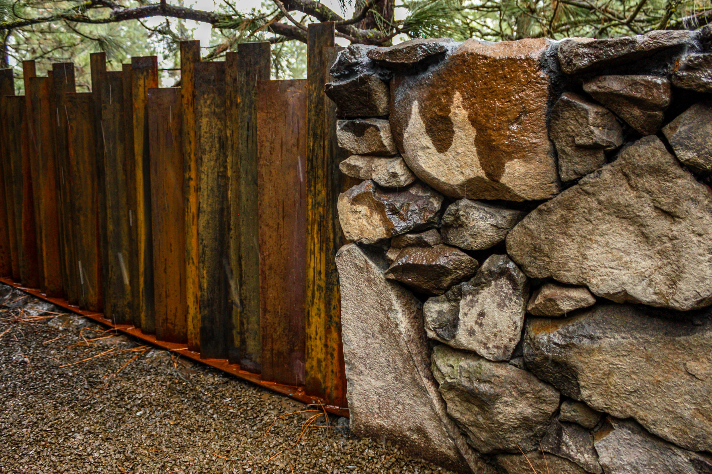 natural basalt wall and corten metal fence on spokane south hill