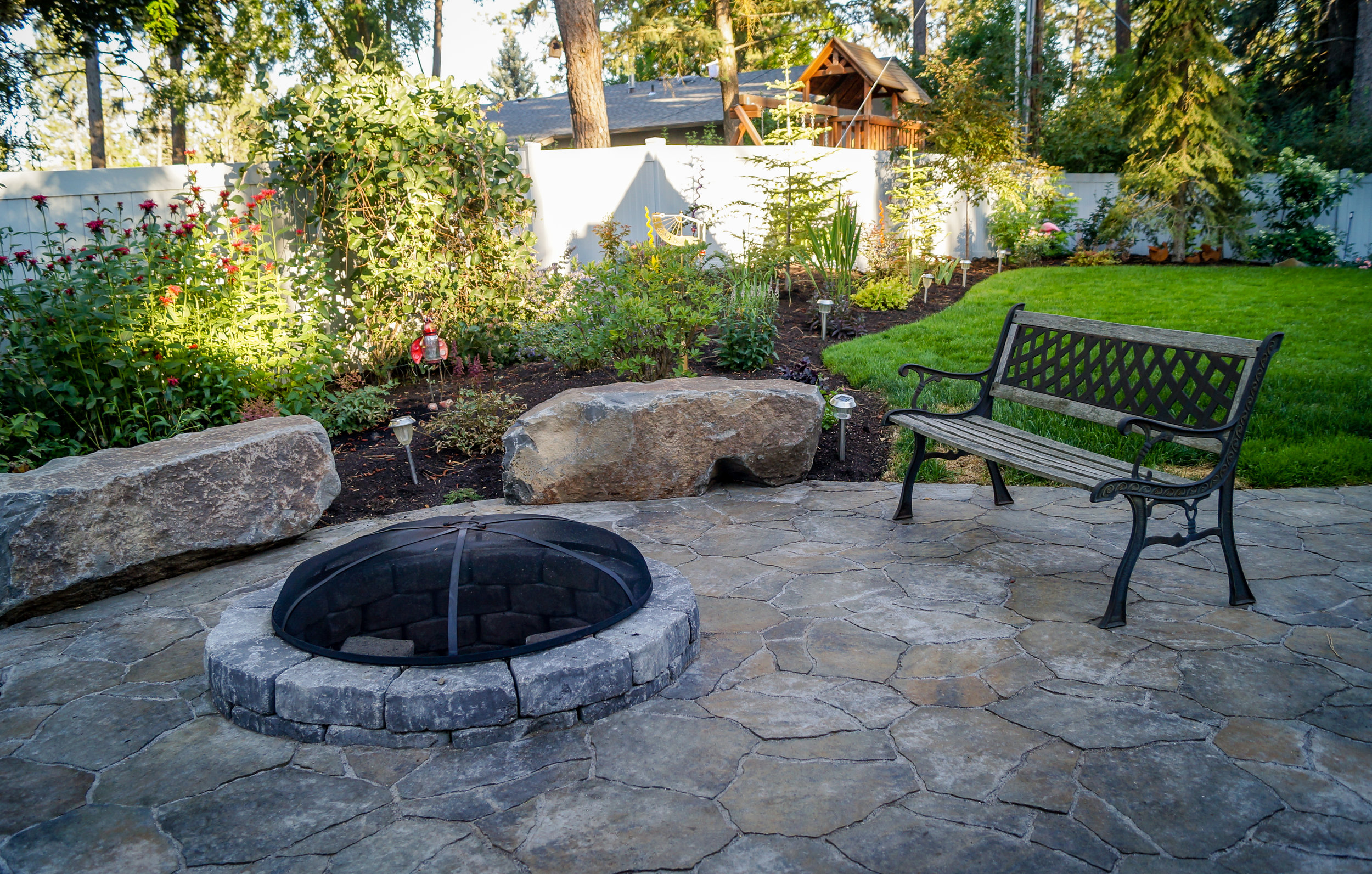 northwest landscaping with stone bench rocks and paver patio around fire pit