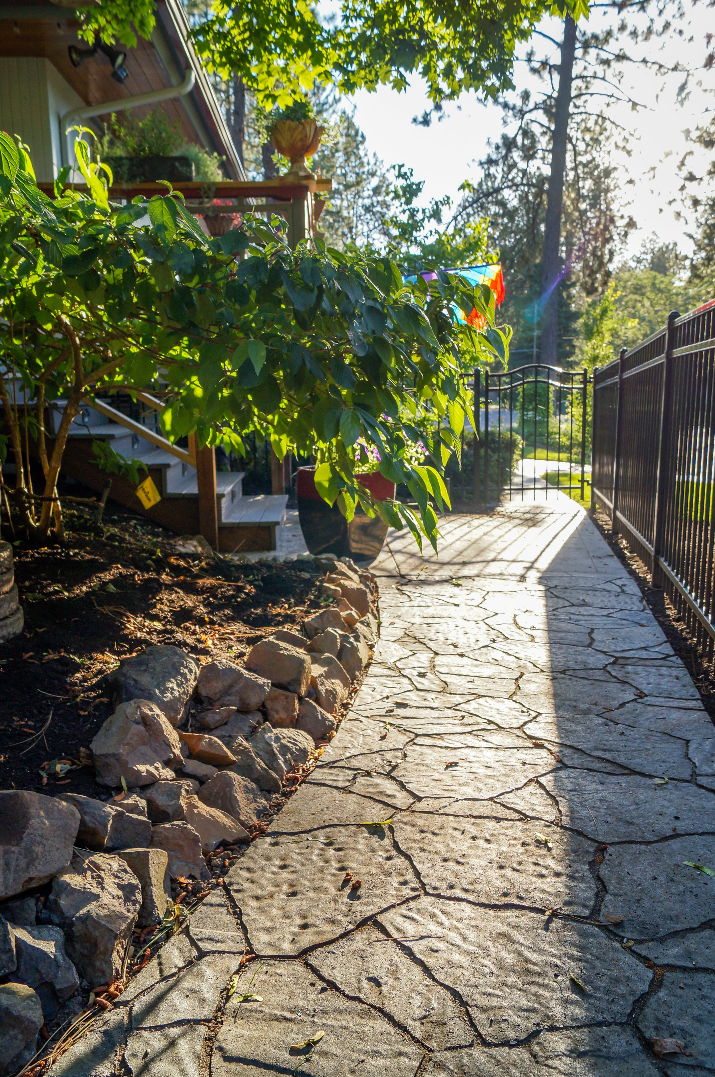 spokane landscape with paver pathway to deck steps on mid century ranch house