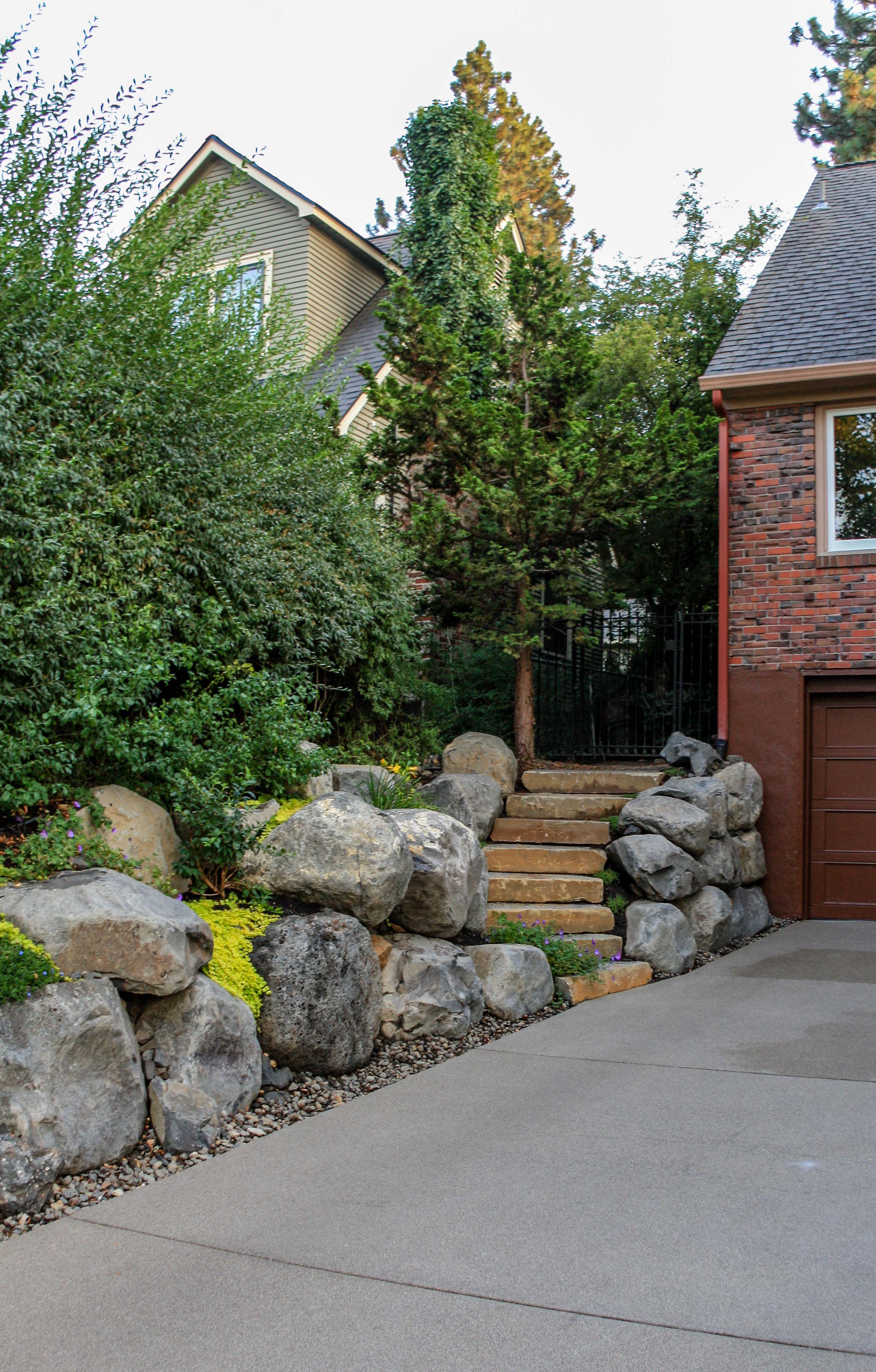 spokane landscaping with boulder retaining walls and sandwashed driveway